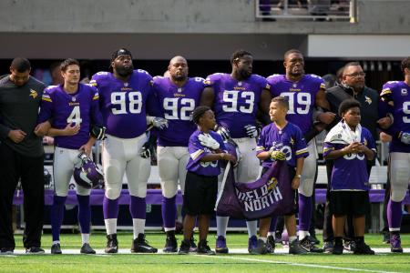 Minnesota Vikings players lock arms during the national anthem before the game against the Tampa Bay Buccaneers