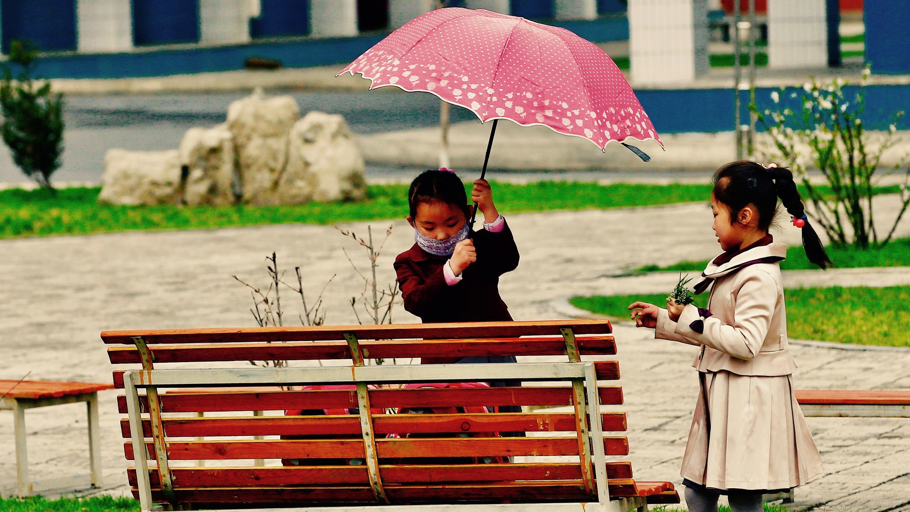 Girl opens umbrella at bench.