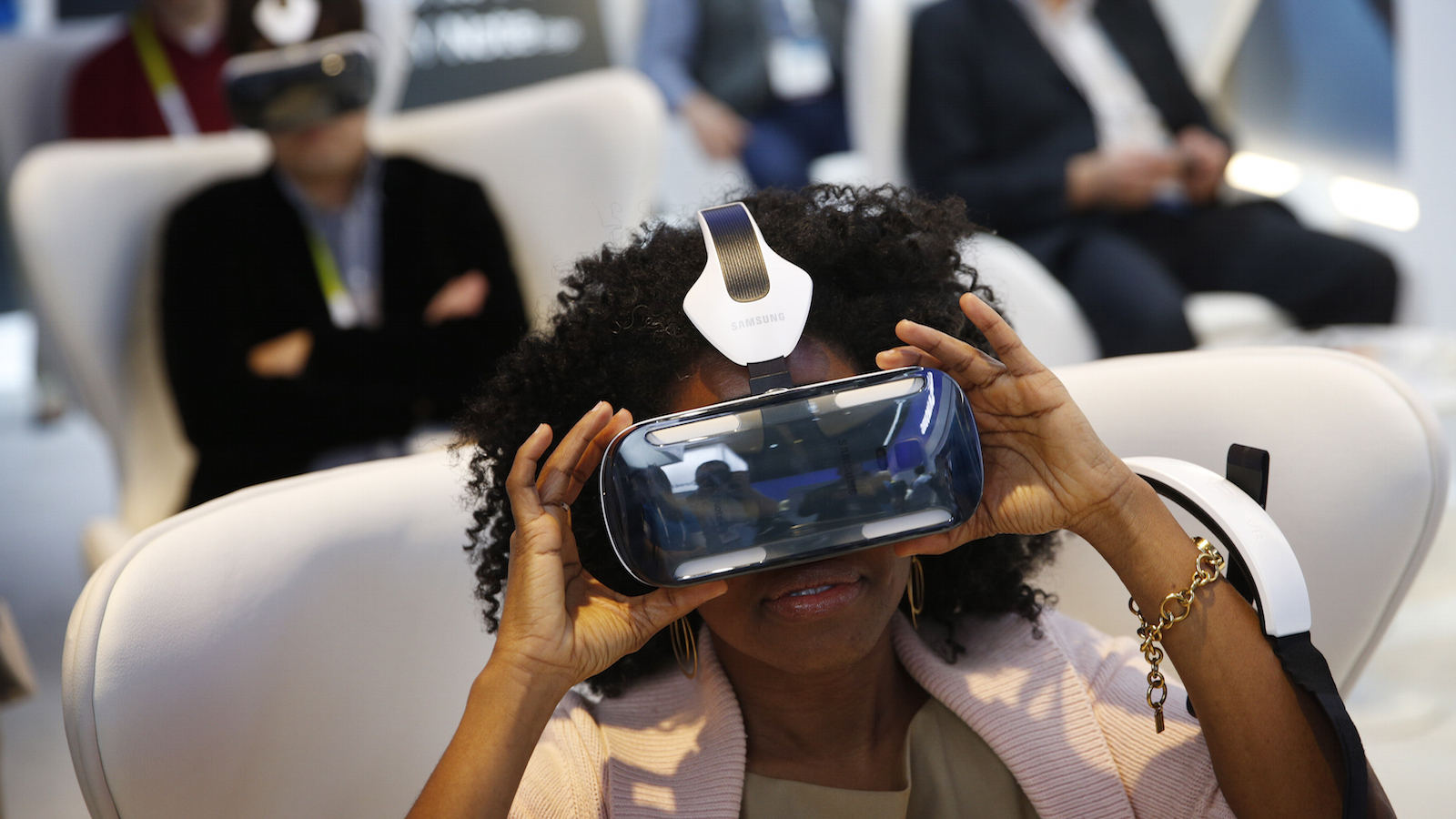FILE - In this Jan. 6, 2015 file photo, Yasmin Moorman looks into the Galaxy Gear VR headset at the Samsung booth during the International CES, in Las Vegas.  While more than 1,500 attendees are expected on Saturday, Aug. 29, 2015, at the VRLA expo, the event probably won't feel very crowded. That's because headset-wearing convention goers will be transported to other worlds during the second-annual celebration of virtual reality at the Los Angeles Convention Center. (AP Photo/John Locher, File)