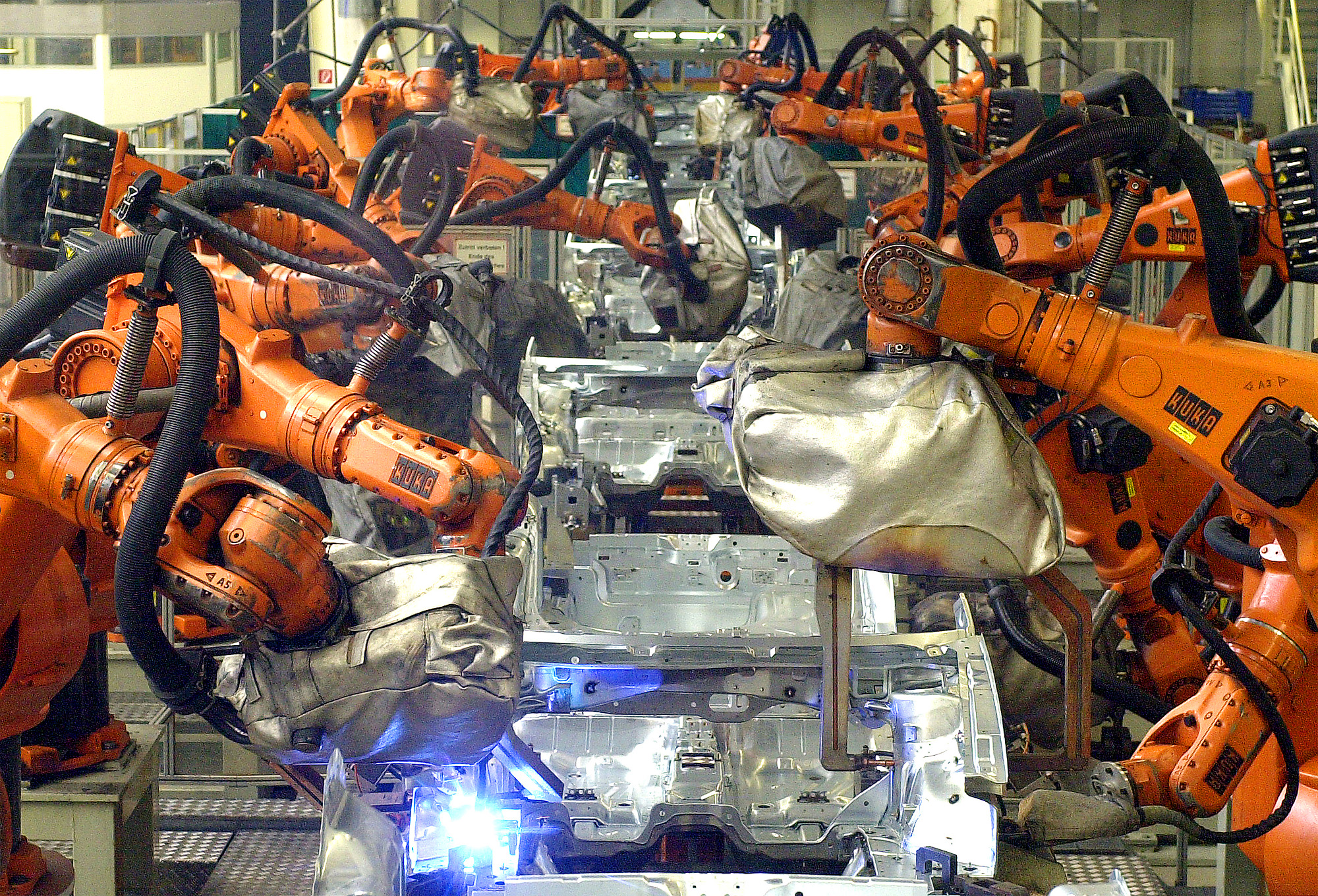 Welding robots at the production line at the plant of German carmaker Volkswagen in Wolfsburg, northern Germany, in this March 4, 2002 picture. A spokesperson of Volkswagen said on Friday, June 20, 2003, it has to halt production in its main factory in Wolfsburg next week as a result of the ongoing strikes in eastern Germany, that block supplying companies. (AP Photo/Fabian Bimmer)