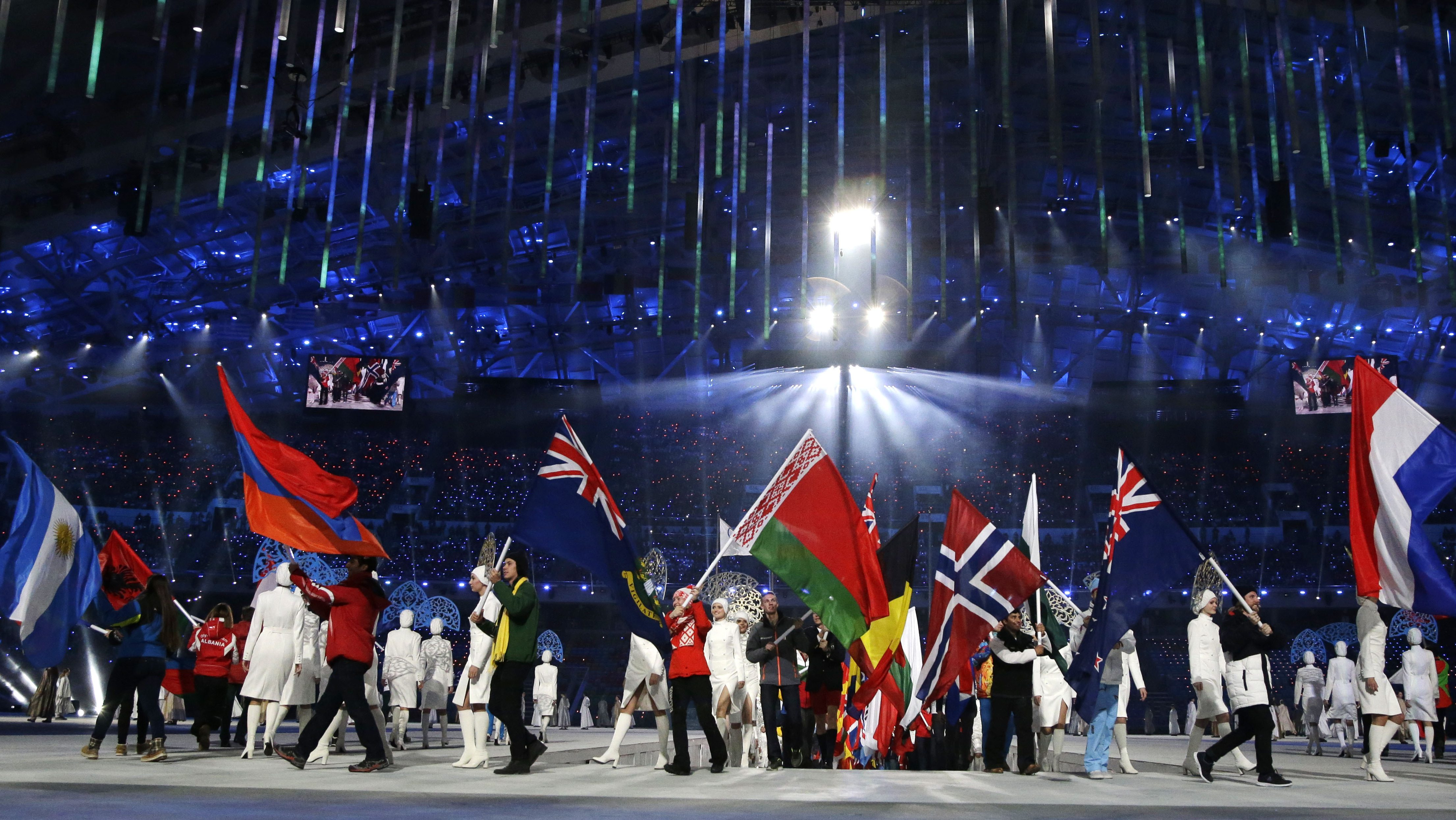 Athletes from various countries carry their national flags as they arrive during the closing ceremony of the 2014 Winter Olympics, Sunday, Feb. 23, 2014, in Sochi, Russia. (AP Photo/Darron Cummings)