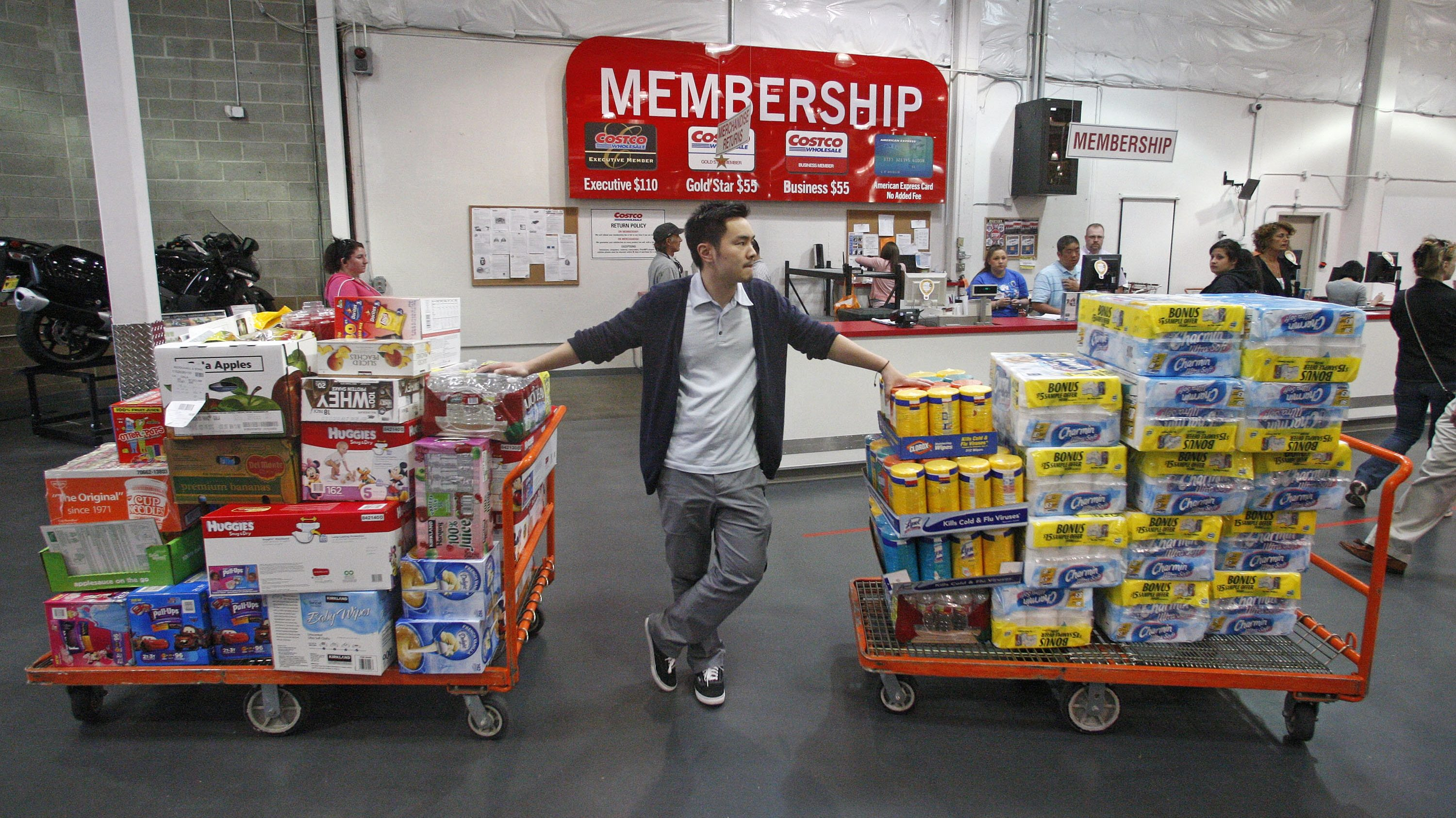 In this Wednesday, May 9, 2012, file photo, David Lee holds on to his carts while shopping at a Costco Wholesale in Portland, Ore. A steep drop in gasoline costs drove down a measure of U.S. wholesale prices in May by the most since July 2009. But outside the food and energy categories, prices increased moderately.