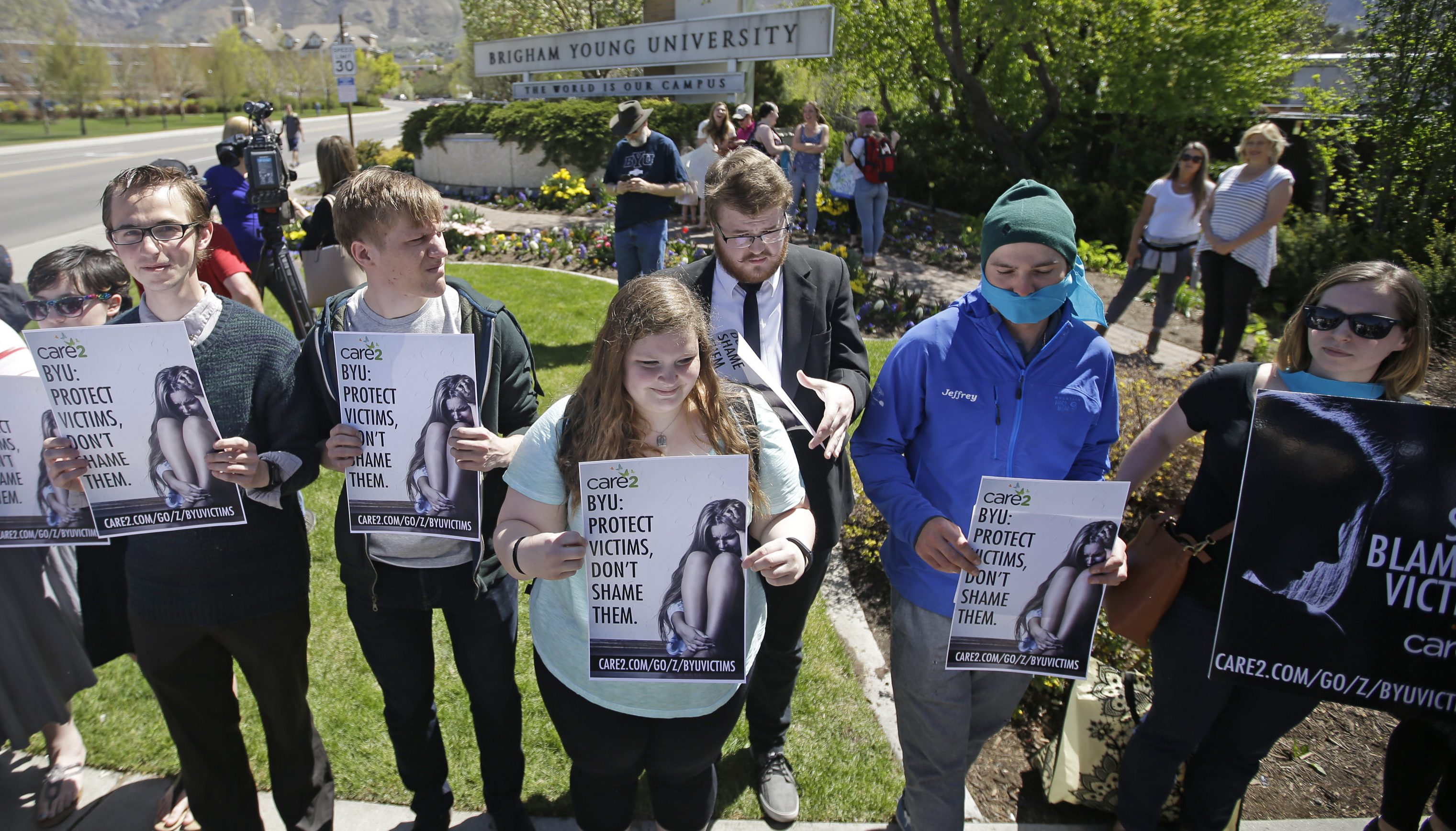 FILE - This April 20, 2016, file photo, protesters stand in solidarity with rape victims on the campus of Brigham Young University during a sexual assault awareness demonstration, in Provo, Utah. BYU announced Wednesday, Oct. 26, 2016, that students who report sexual assault will no longer be investigated for possible violations of the Mormon-owned school's strict honor code that bans such things as alcohol use. (AP Photo/Rick Bowmer, File)