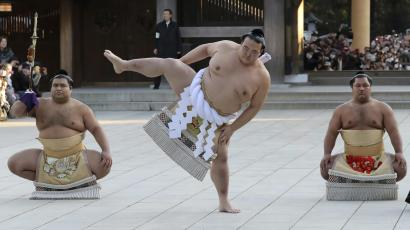 """In this Friday, Jan. 27, 2017 photo, newly-promoted sumo grand champion Kisenosato performs his ring entry form at the Meiji Shrine in Tokyo. Kisenosato is the first Japanese wrestler to earn the coveted rank of """"yokozuna,"""" grand champion, since 1998. Accompanying Kisenosato are sward-holder Takayasu, left, and dew-sweeper Shohozan, right. (AP Photo/Eugene Hoshiko, File)"""
