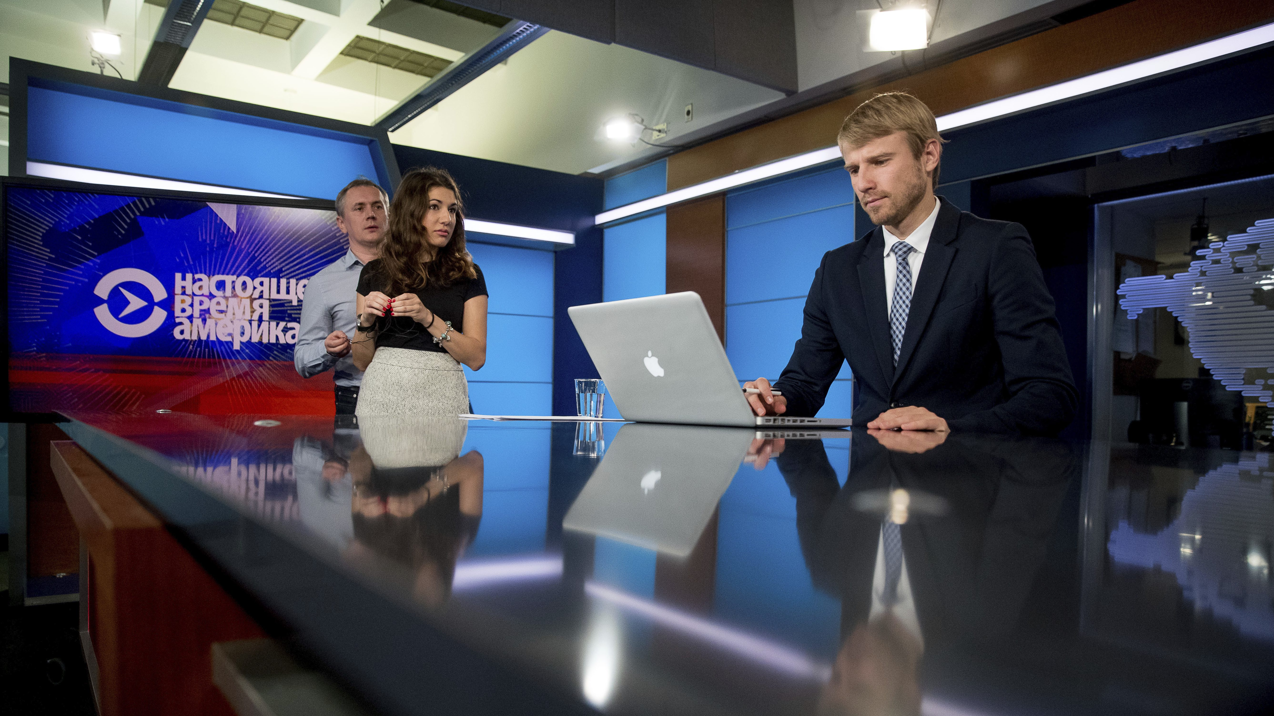 Current Time America news anchor Ihar Tsikhanenko, right, prepares for a broadcast in the offices of Voice of America in Washington, Wednesday, Feb. 8, 2017. Two U.S. government-funded news outlets are launching Current Time, a global Russian-language TV network aimed at providing an alternative to slick, Kremlin-controlled media that critics say spread propaganda and misinformation. (AP Photo/Andrew Harnik)