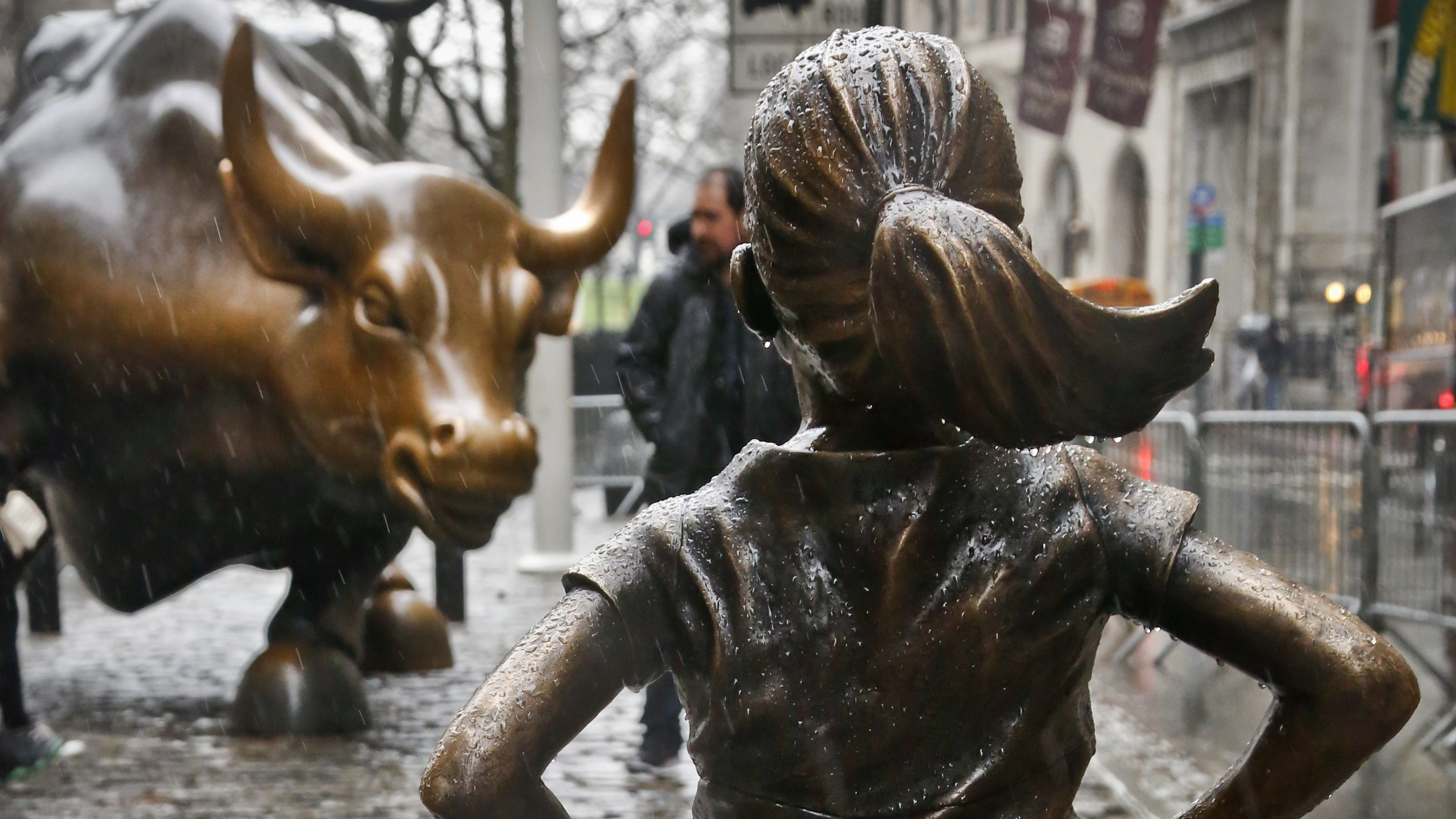 """The """"Fearless Girl"""" statue, created by Kristen Visbal, stands across from the """"Charging Bull"""" statue, Monday, March 27, 2017, in New York. Mayor Bill de Blasio says the popular statue of a young girl will be allowed to remain through February 2018. (AP Photo/Bebeto Matthews)"""