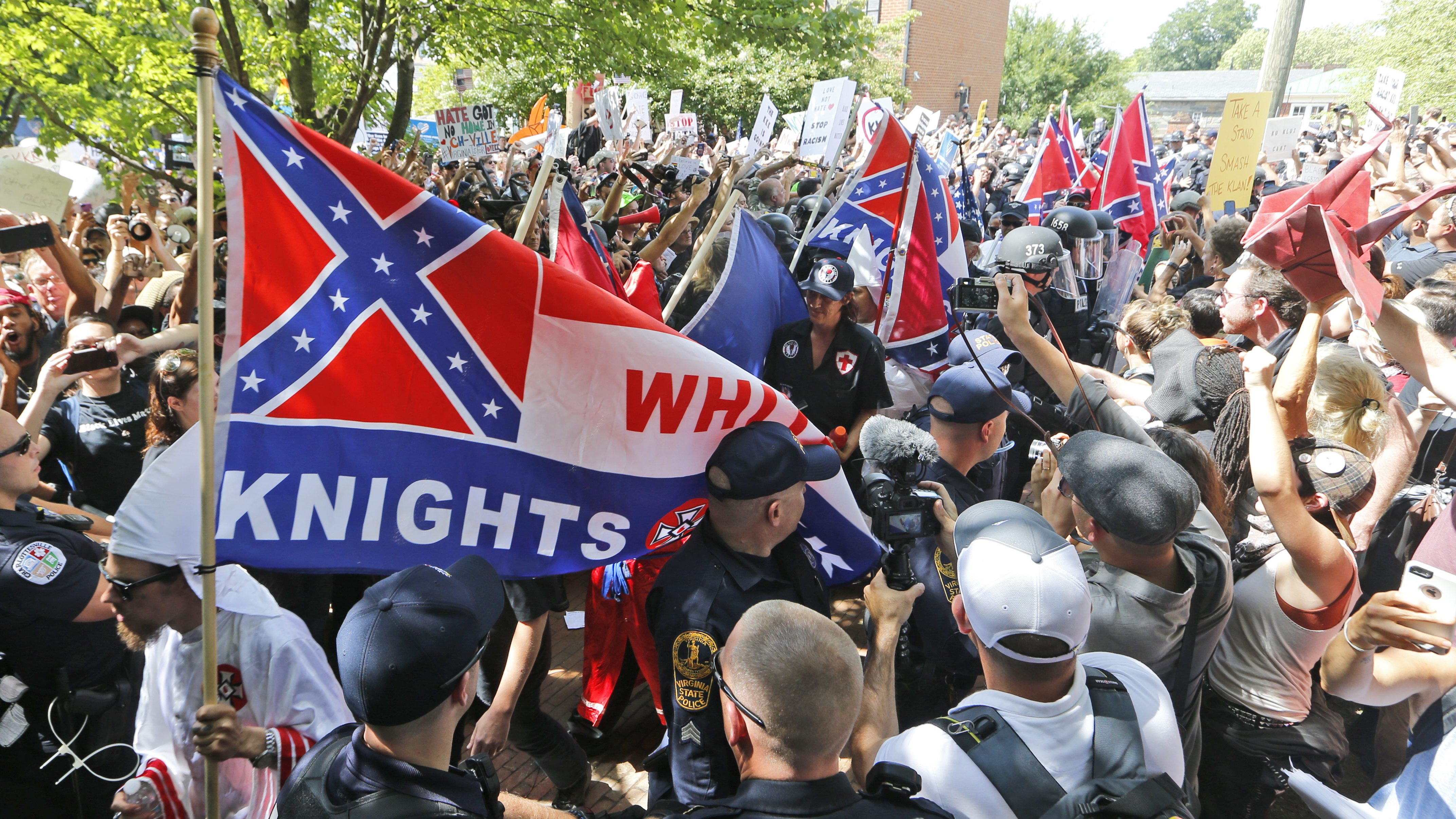 This July 8, 2017 photo shows members of the KKK escorted by police past a large group of protesters during a KKK rally in Charlottesville, Va.  Some white Southerners are again advocating for what the Confederacy tried and failed to do in the 1860s: secession from the Union. So-called Southern nationalists are within the group of demonstrators who are fighting the removal of Confederate monuments around the South. They say it's time for Southern states to secede again and become independent of the United States.(AP Photo/Steve Helber)