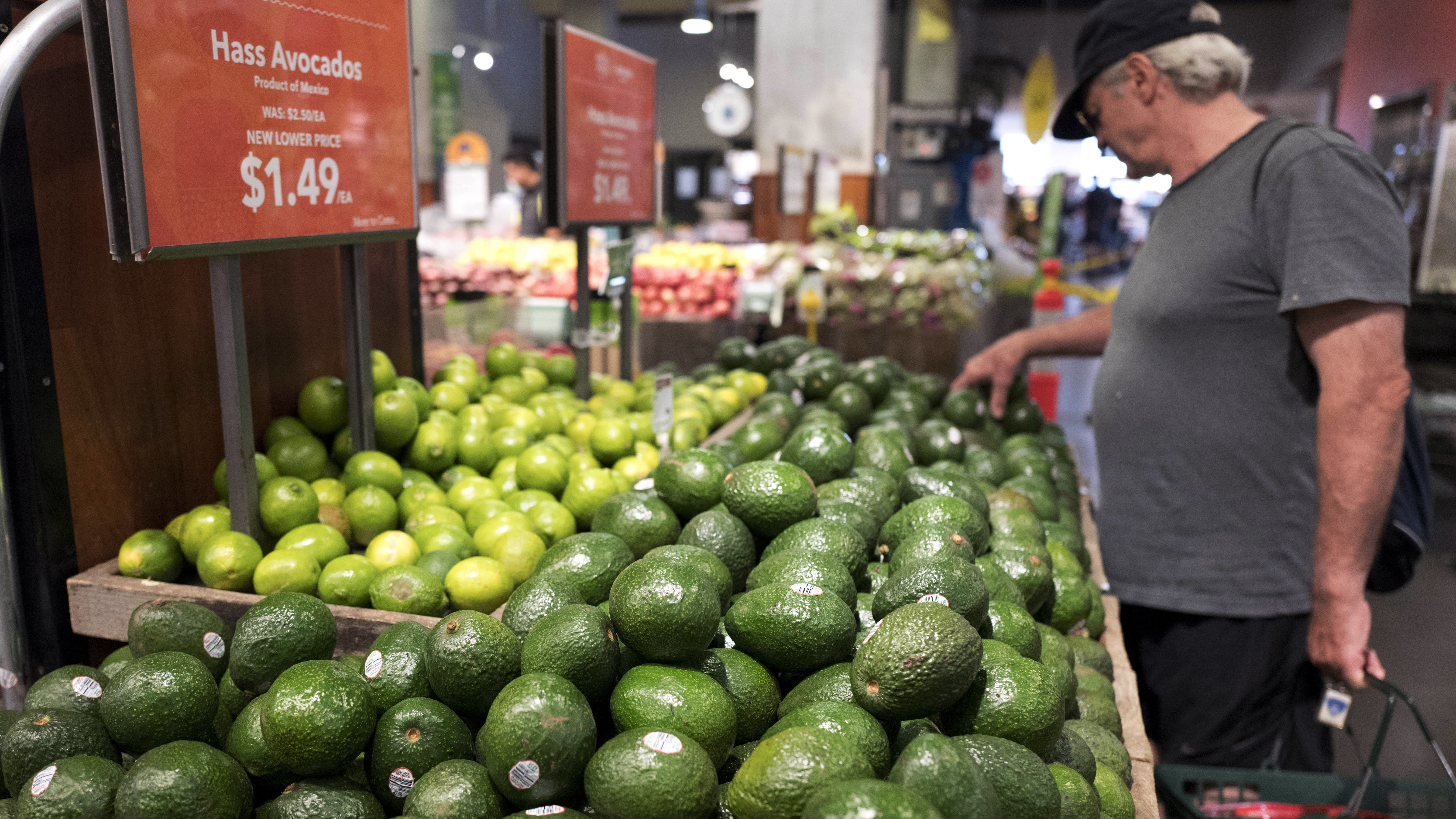 A man shops for avocados at a Whole Foods Market, in New York.