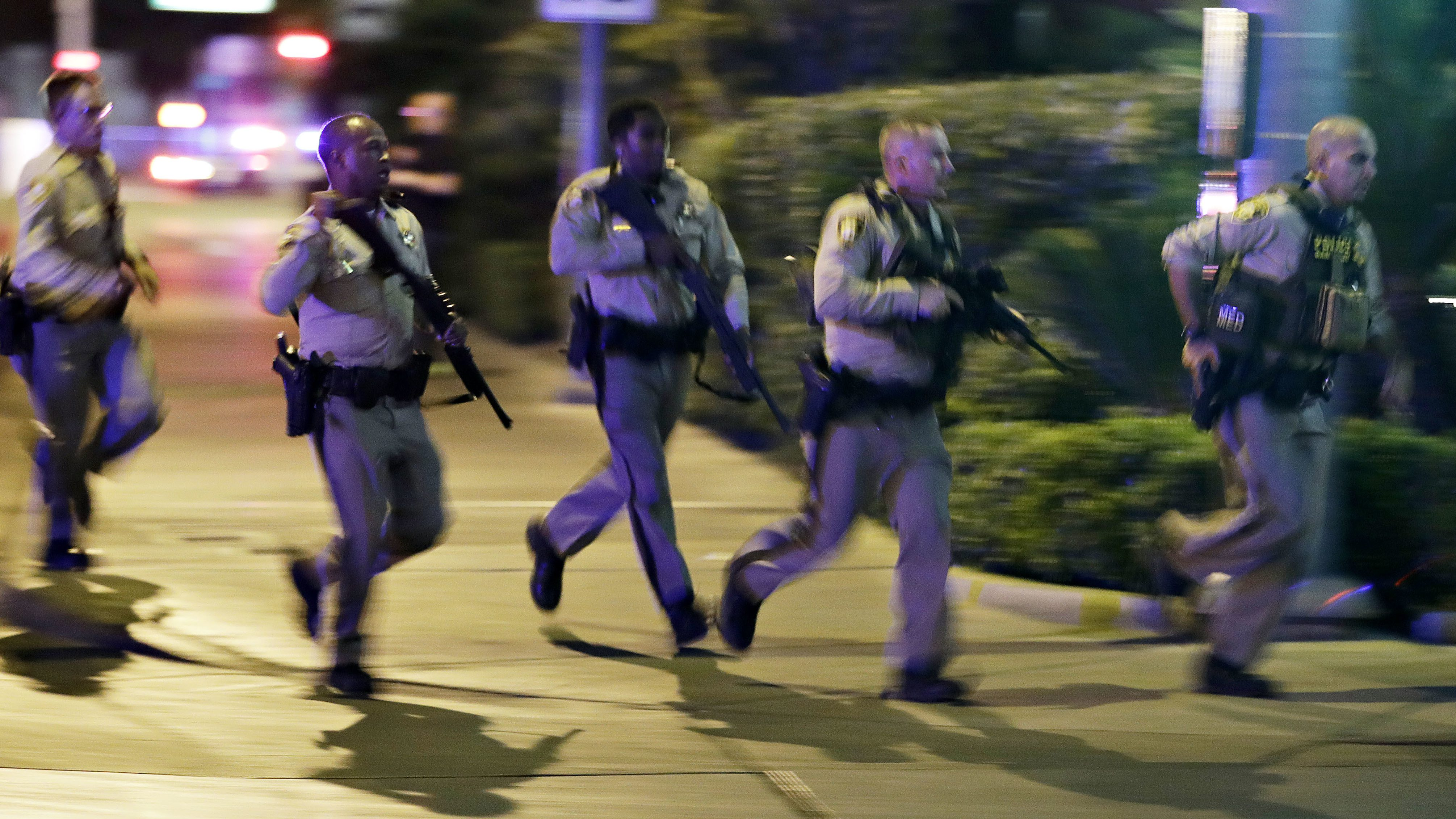 Police run to cover at the scene of a shooting near the Mandalay Bay resort and casino on the Las Vegas Strip