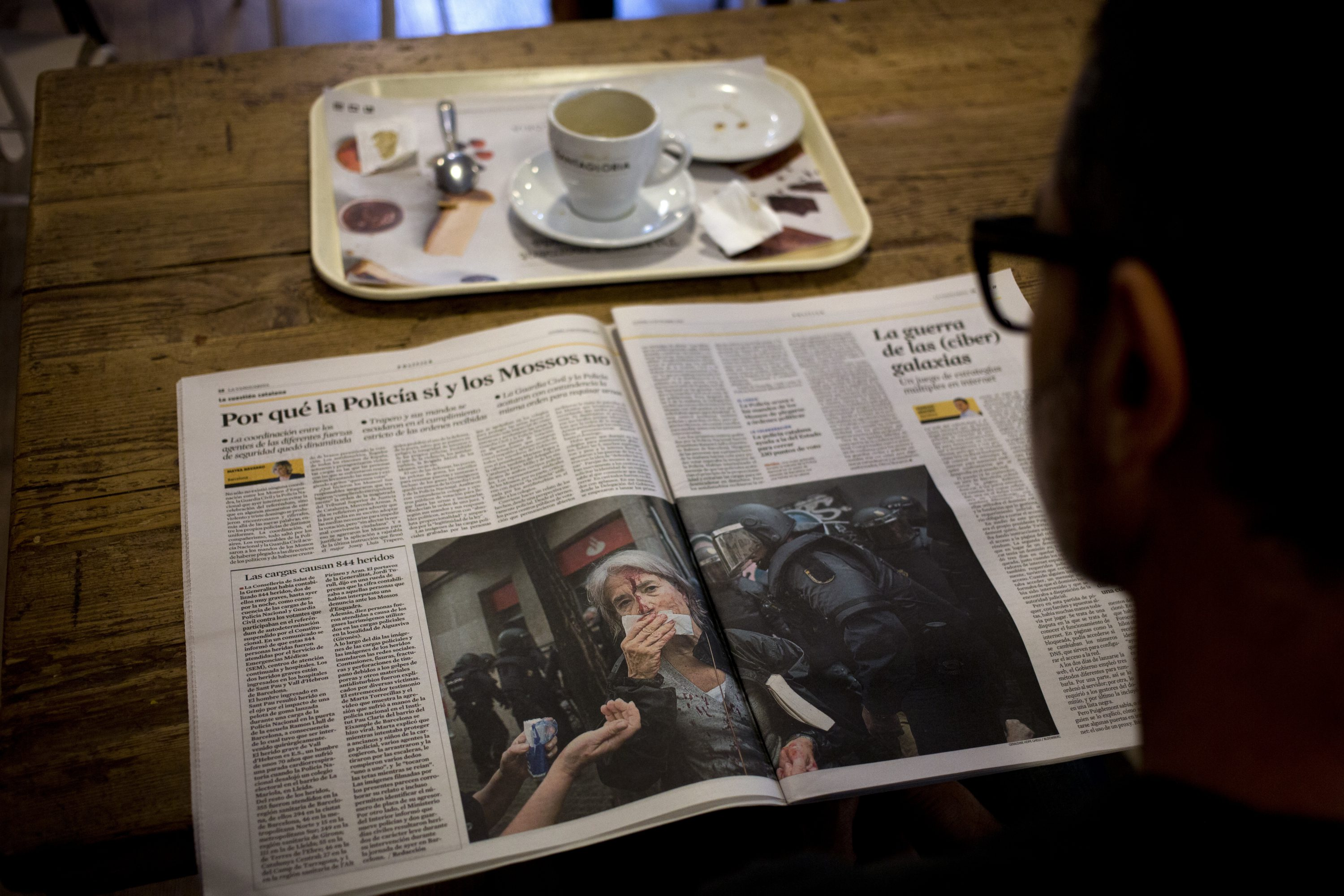 A man reads a newspaper featuring the news following a disputed referendum marred by violence in Barcelona, Spain, Monday, Oct. 2, 2017. Catalan leaders accused Spanish police of brutality and repression while the Spanish government praised the security forces for behaving firmly and proportionately. Videos and photographs of the police actions were on the front page of news media outlets around the world.