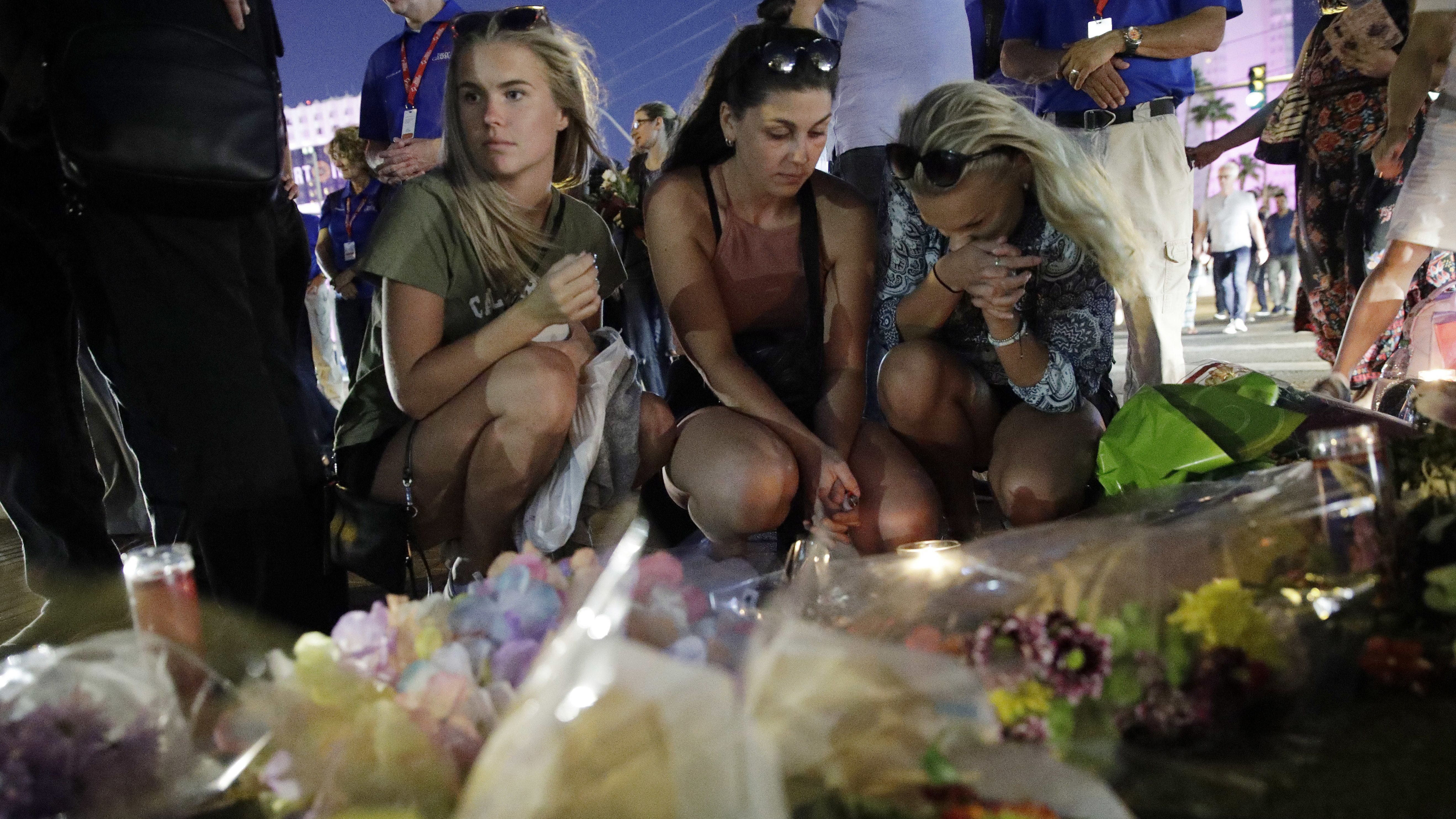 People pause at a memorial set up for victims of a mass shooting in Las Vegas, Nev., on Tuesday, Oct. 3, 2017. A gunman opened fire on an outdoor music concert on Sunday. It was the deadliest mass shooting in modern U.S. history, with dozens of people killed and hundreds injured, some by gunfire, some during the chaotic escape. (AP Photo/John Locher)