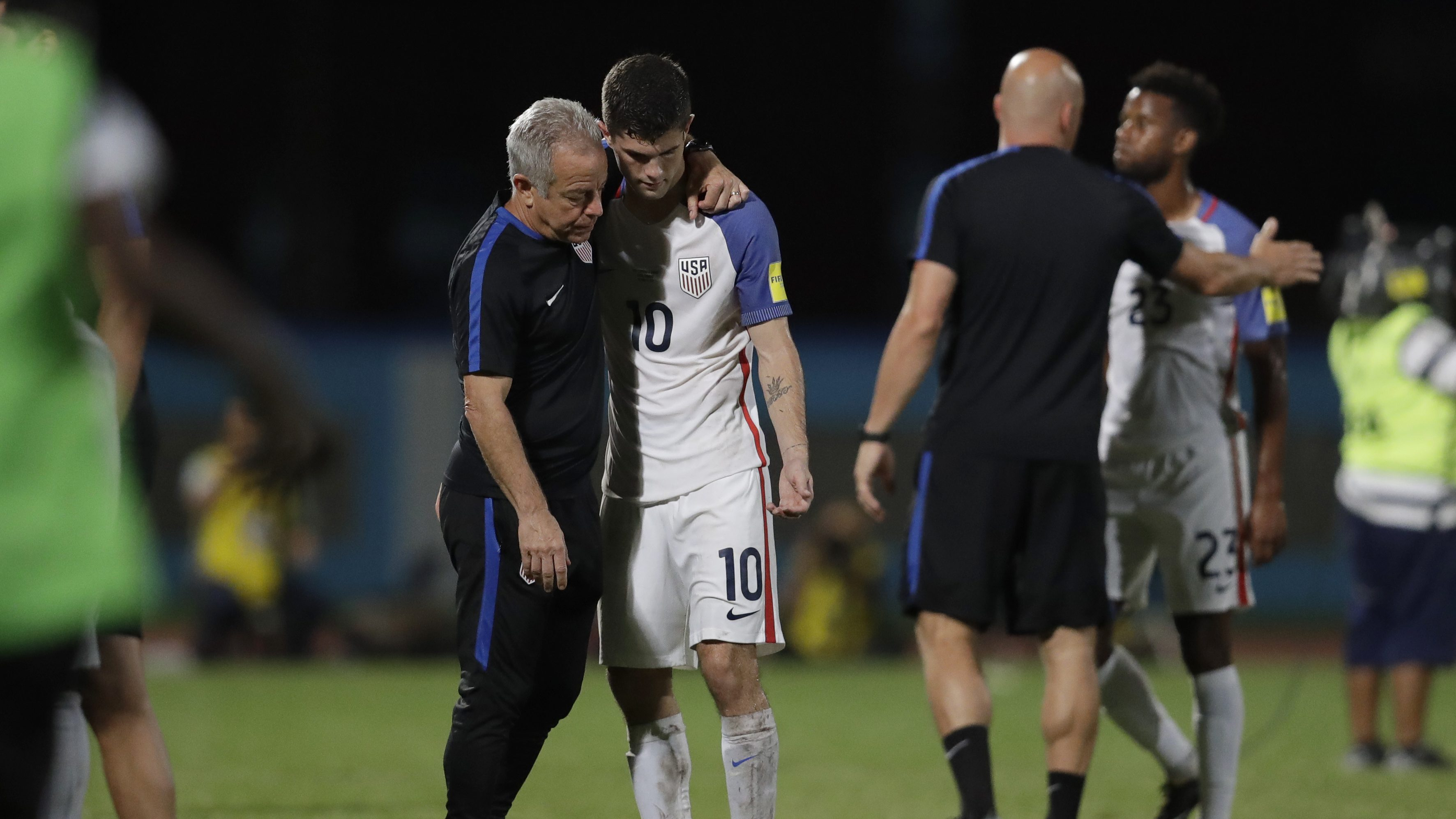 United States' Christian Pulisic, (10) is comforted after losing 2-1 against Trinidad and Tobago during a 2018 World Cup qualifying soccer match in Couva, Trinidad, Tuesday, Oct. 10, 2017.