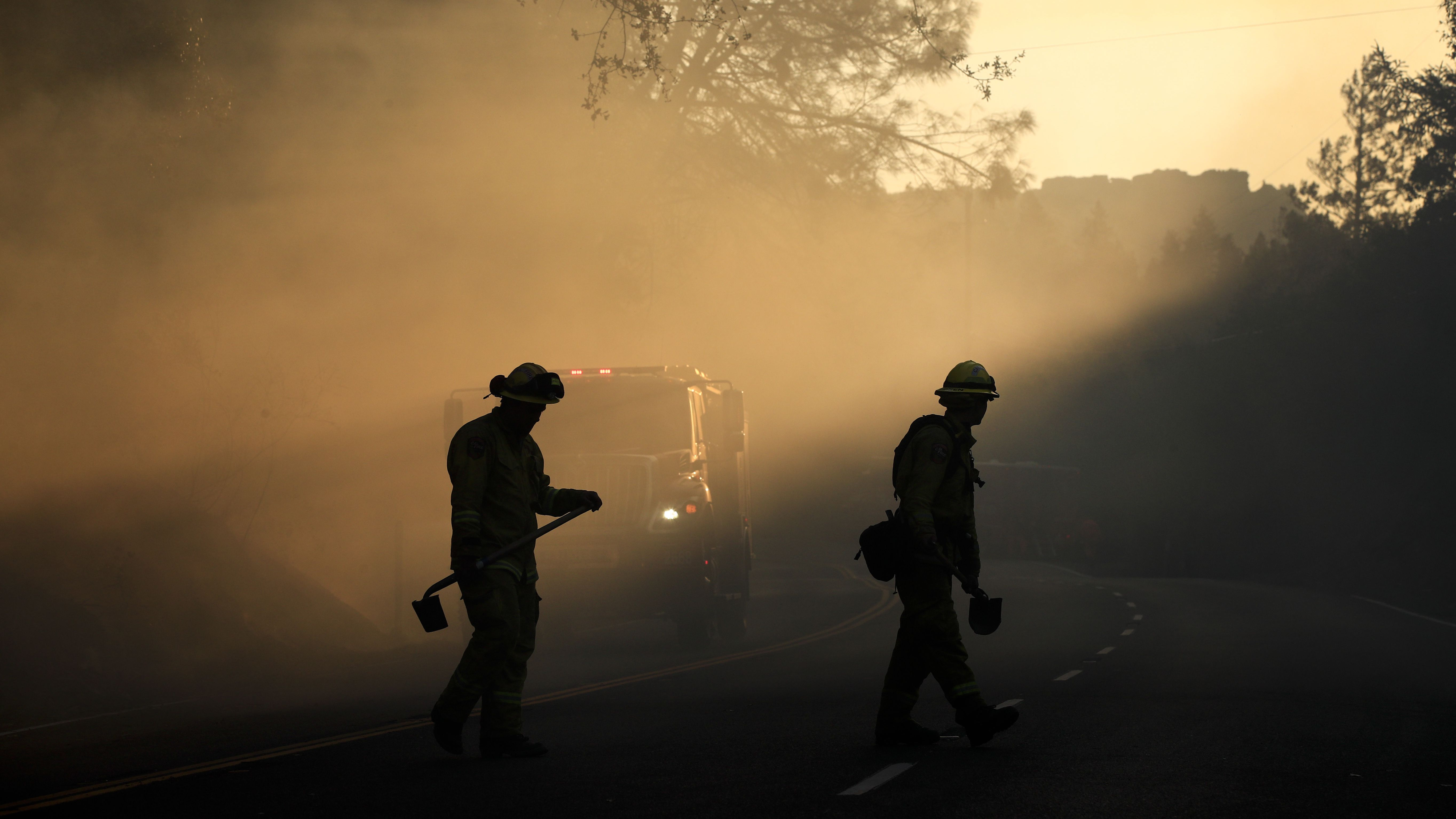 Two firefighters watch for spot fires Friday, Oct. 13, 2017, near Calistoga, Calif. Firefighters gained some ground on a blaze burning in the heart of California's wine country but face another tough day ahead with low humidity and high winds expected to return.