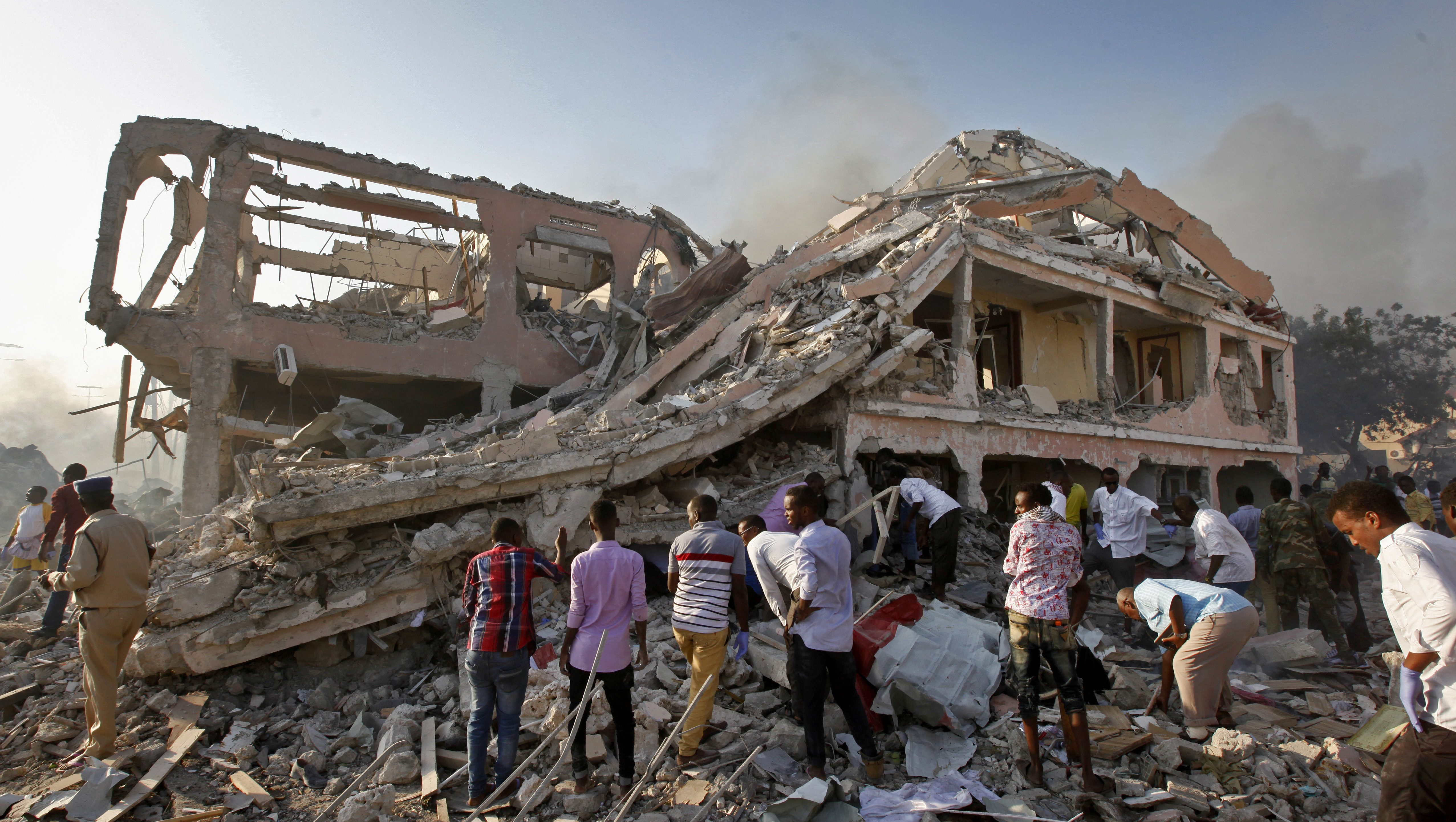 Somalis gather and search for survivors by destroyed buildings at the scene of a blast in the capital Mogadishu, Somalia Saturday, Oct. 14, 2017. A huge explosion from a truck bomb has killed at least 20 people in Somalia's capital, police said Saturday, as shaken residents called it the most powerful blast they'd heard in years.