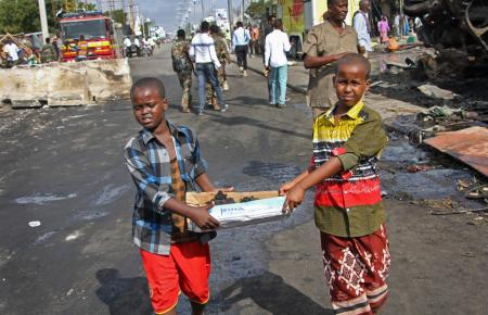 Somali children assist other civilians and security forces in their rescue efforts by carrying away unidentified charred human remains in a cardboard box, to clear the scene of Saturday's blast, in Mogadishu, Somalia.