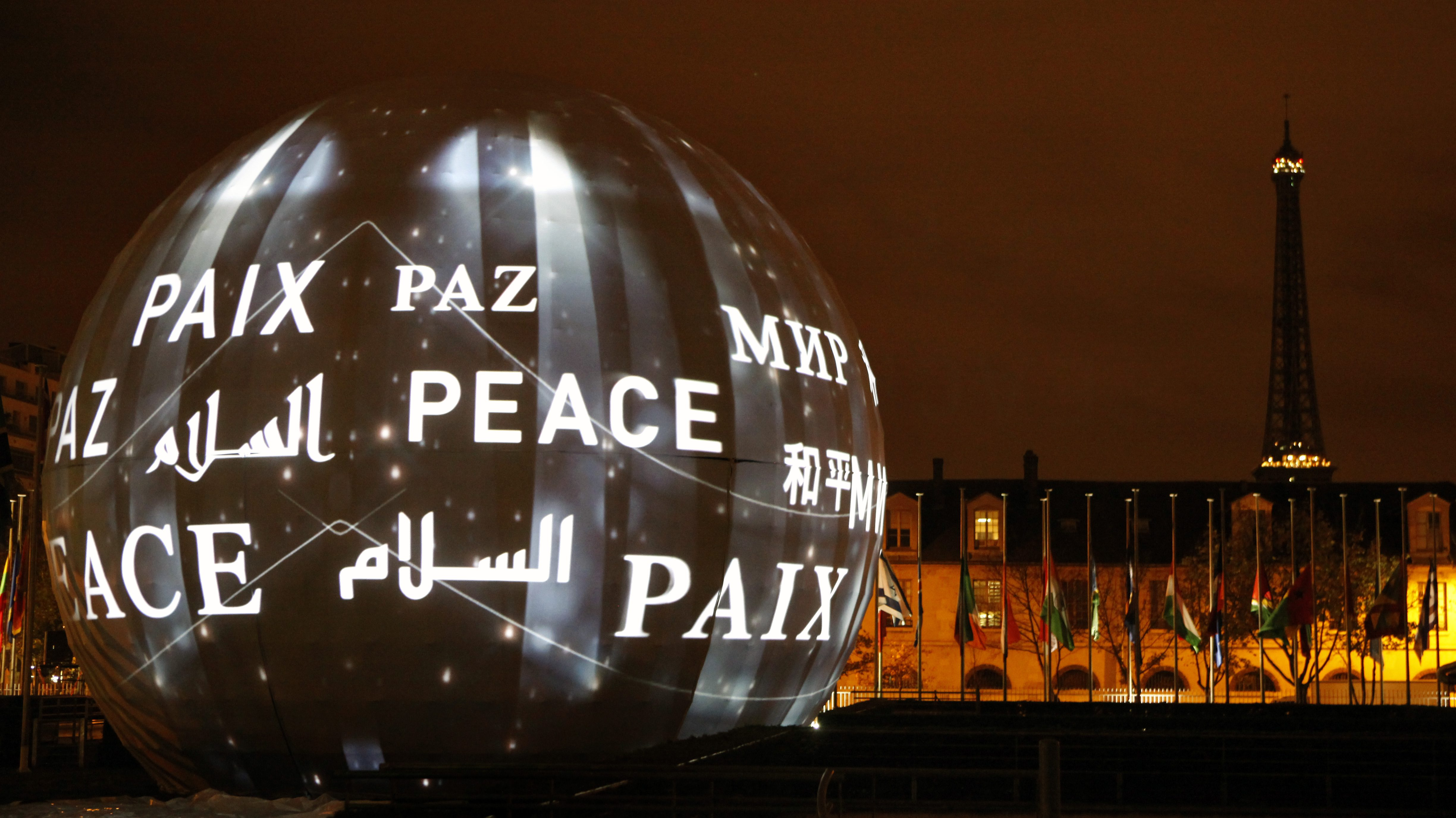The word peace in the six official languages of the organization is projected at UNESCO headquarters in Paris, France, Saturday, Nov. 14, 2015. French President Francois Hollande said more than 120 people died Friday night in shootings at Paris cafes, suicide bombings near France's national stadium and a hostage-taking slaughter inside a concert hall. (AP Photo/Michel Spingler)