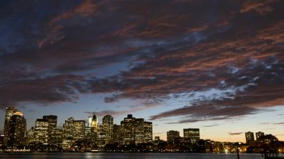 The sunset illuminates clouds over Boston harbor and the city skyline
