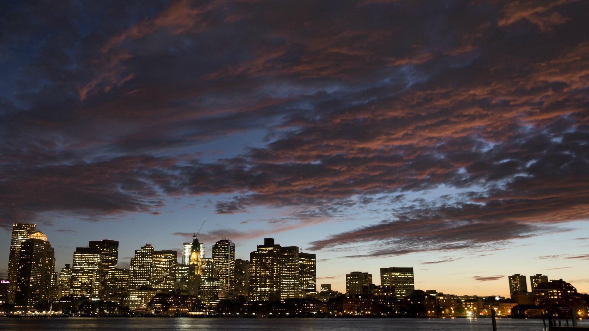 The sunset illuminates clouds over Boston harbor and the city skyline