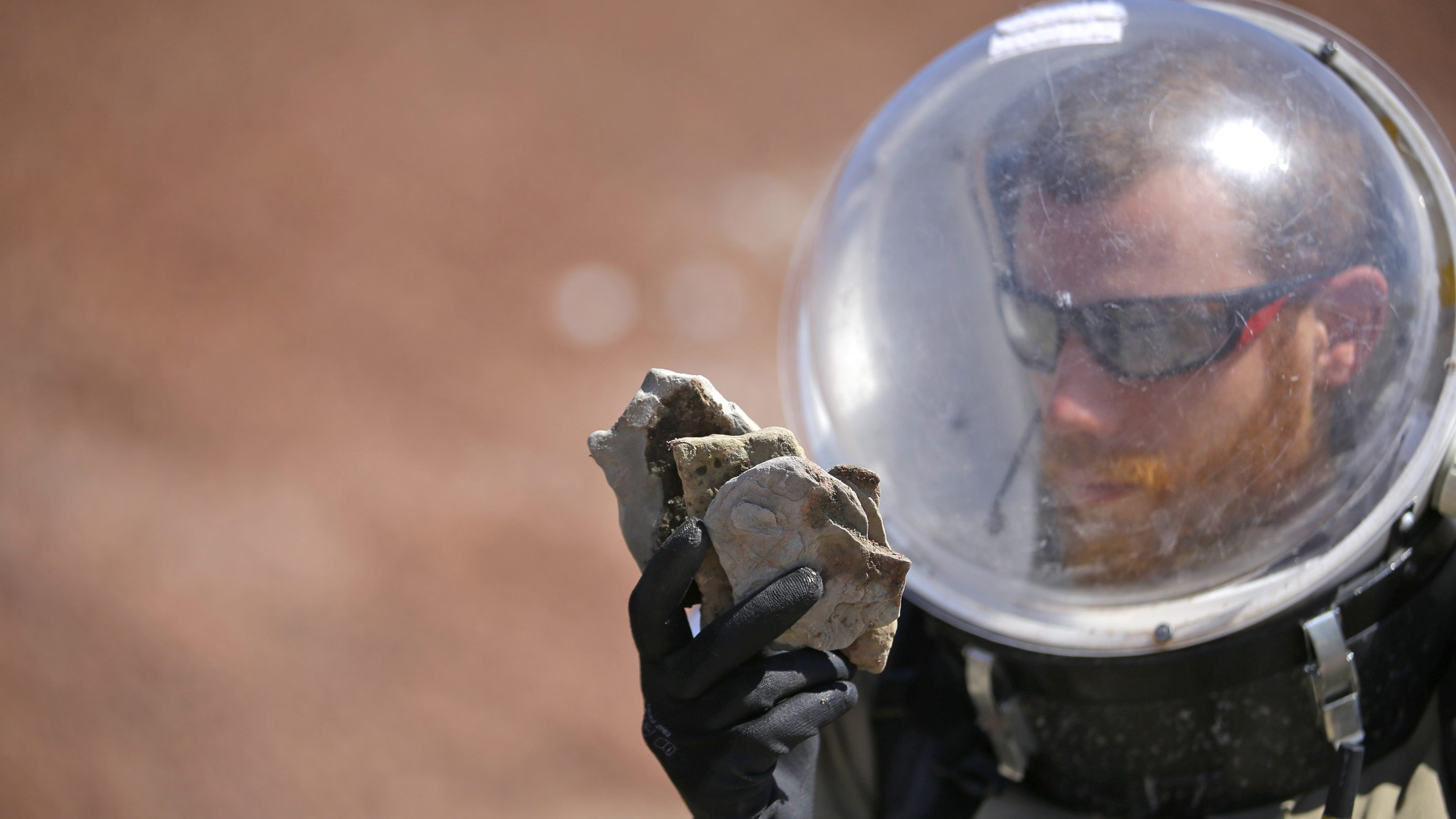 In this photo taken on Saturday, April 18, 2015, Florian Commans, crew biologist and greenhab officier, of Crew 153, studies a collection of rocks near the Mars Desert Research Station, in Hanksville, Utah. This isn't Mars, but it's resemblance to the red planet has made it a hot spot for teams of geologists, biologists and engineers from around the world who have been coming for more than a decade to simulate missions to the mysterious planet in hopes of providing critical research to for future trips to Mars.