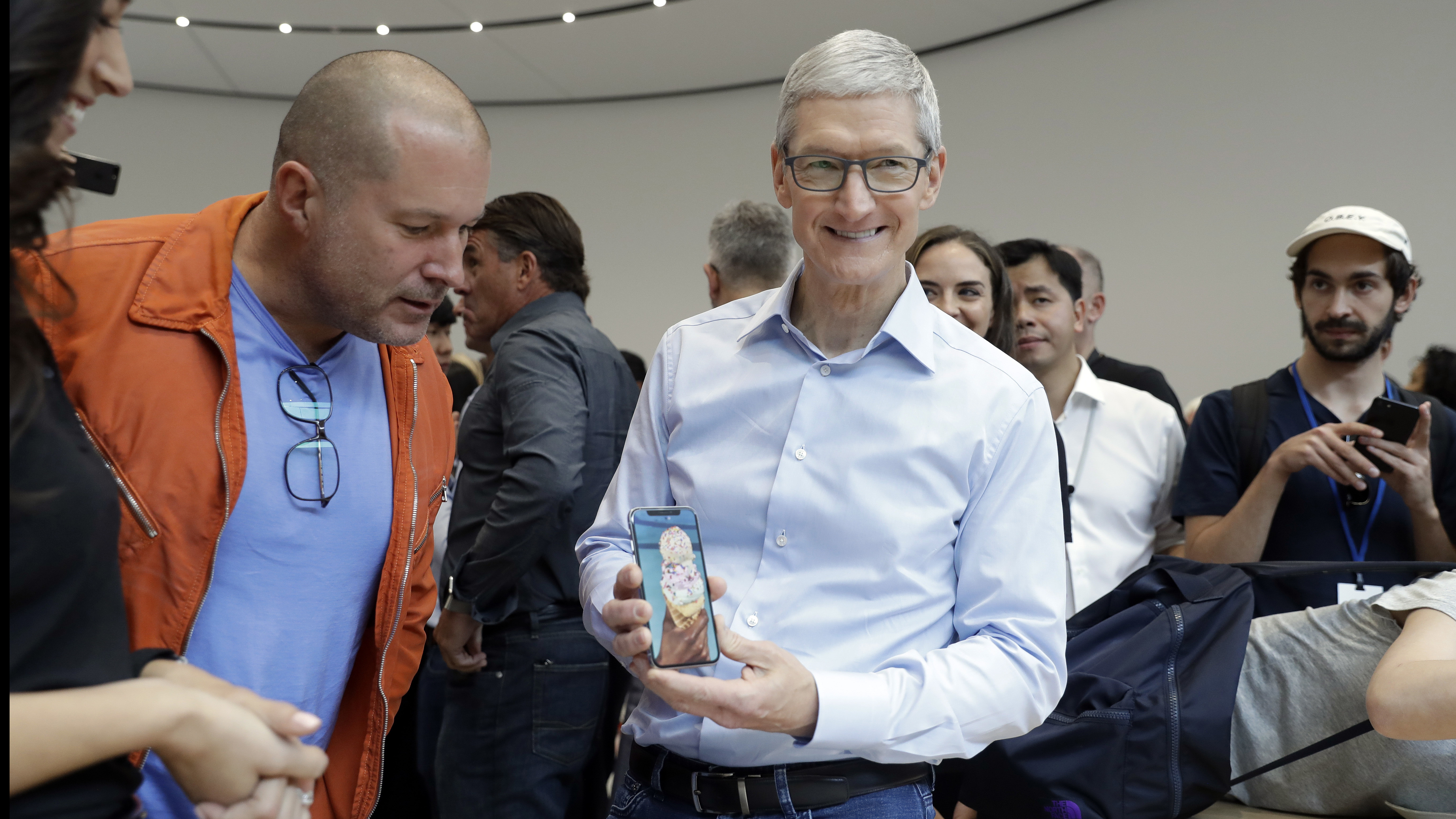 Apple CEO Tim Cook, right, and Jonathan Ive, Chief Design Officer shows the new iPhone X in the showroom after the new product announcement at the Steve Jobs Theater on the new Apple campus on Tuesday, Sept. 12, 2017, in Cupertino, Calif. (AP Photo/Marcio Jose Sanchez)