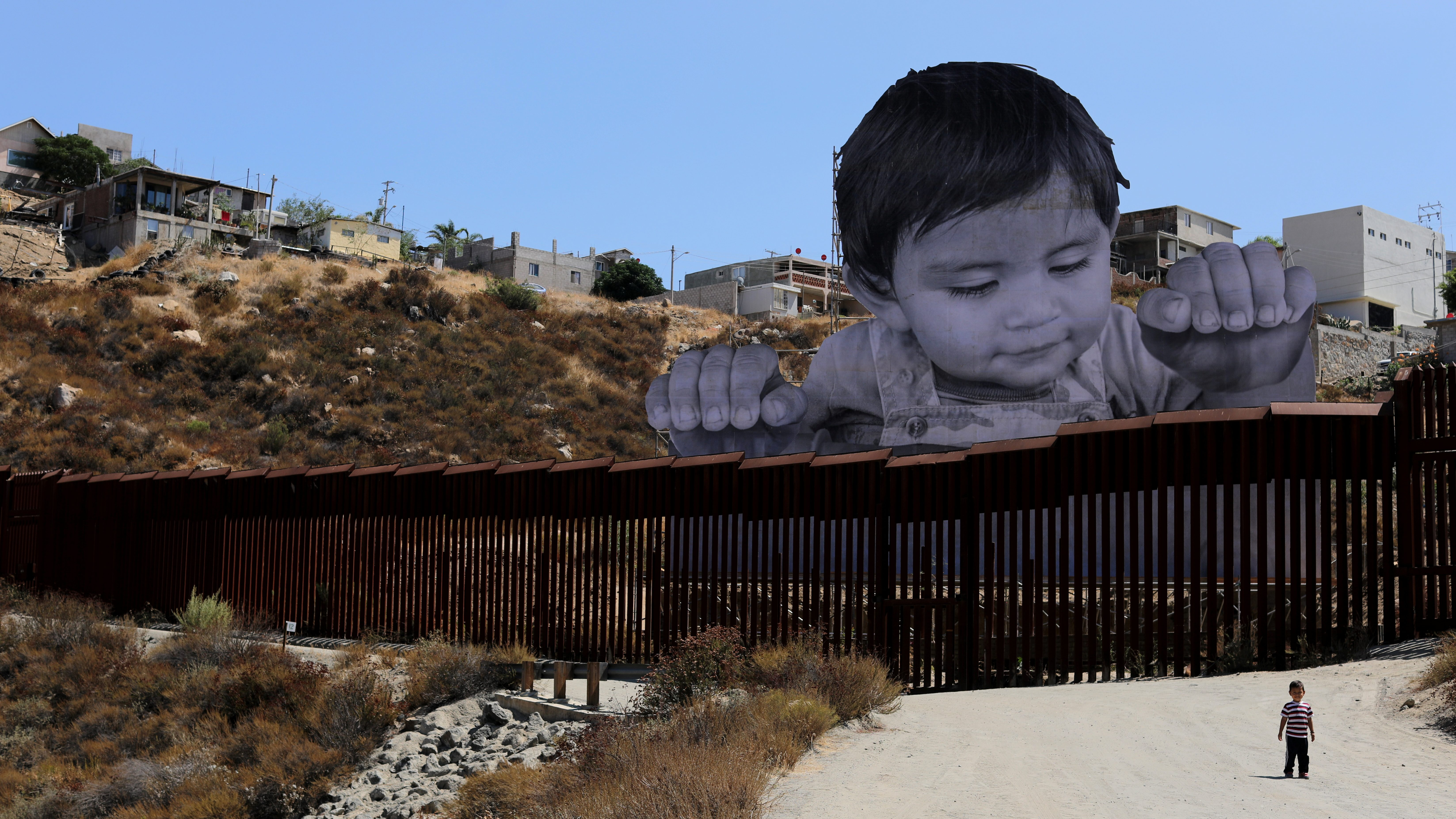 French artist JR's image of an inquisitive baby looking into the United States over the U.S.- Mexico border wall towards Tecate, California,