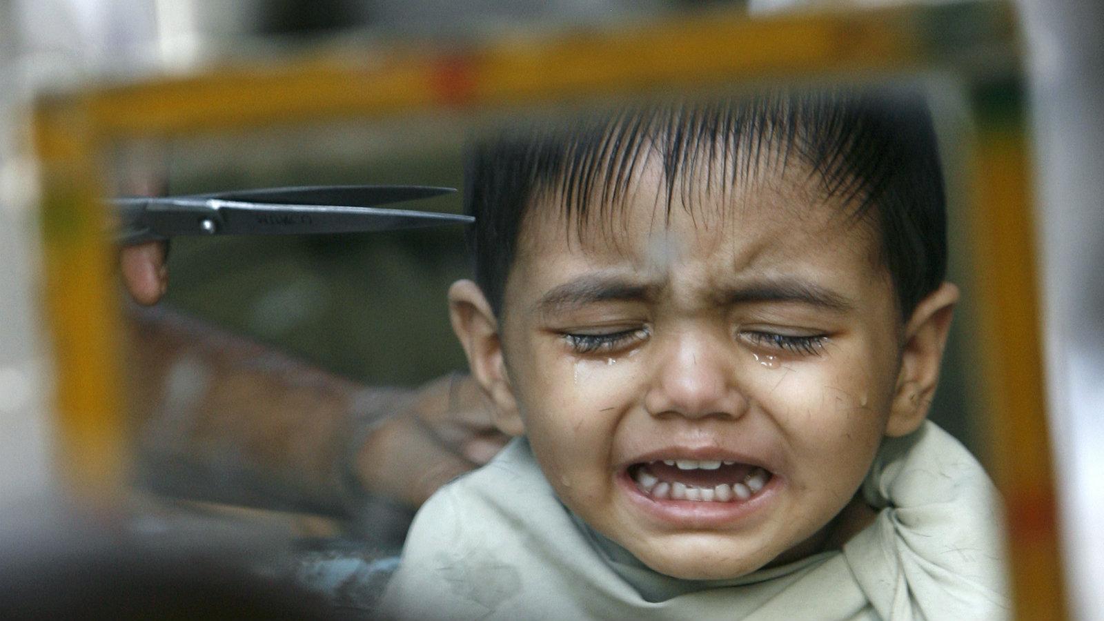 A child in Delhi gets a hair cut at a roadside barber shop.