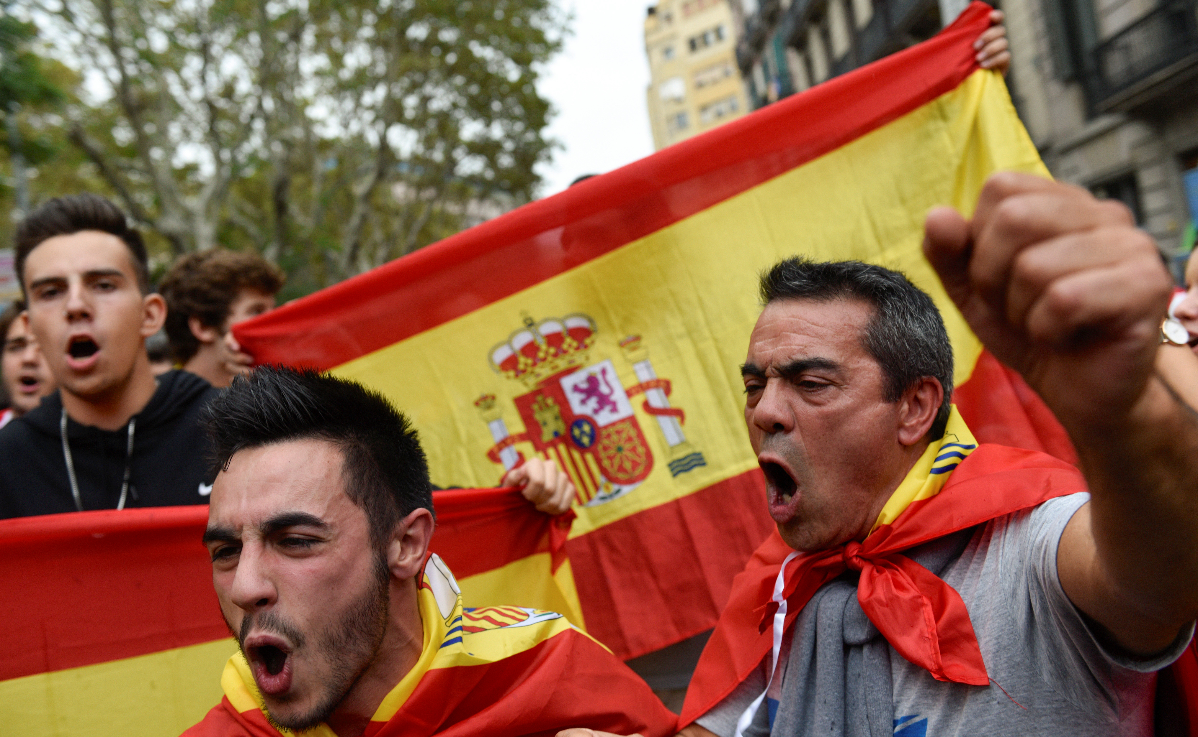 People shout in front of Spanish flags during a demonstration in favour of a unified Spain a day before the banned October 1 independence referendum, in Barcelona