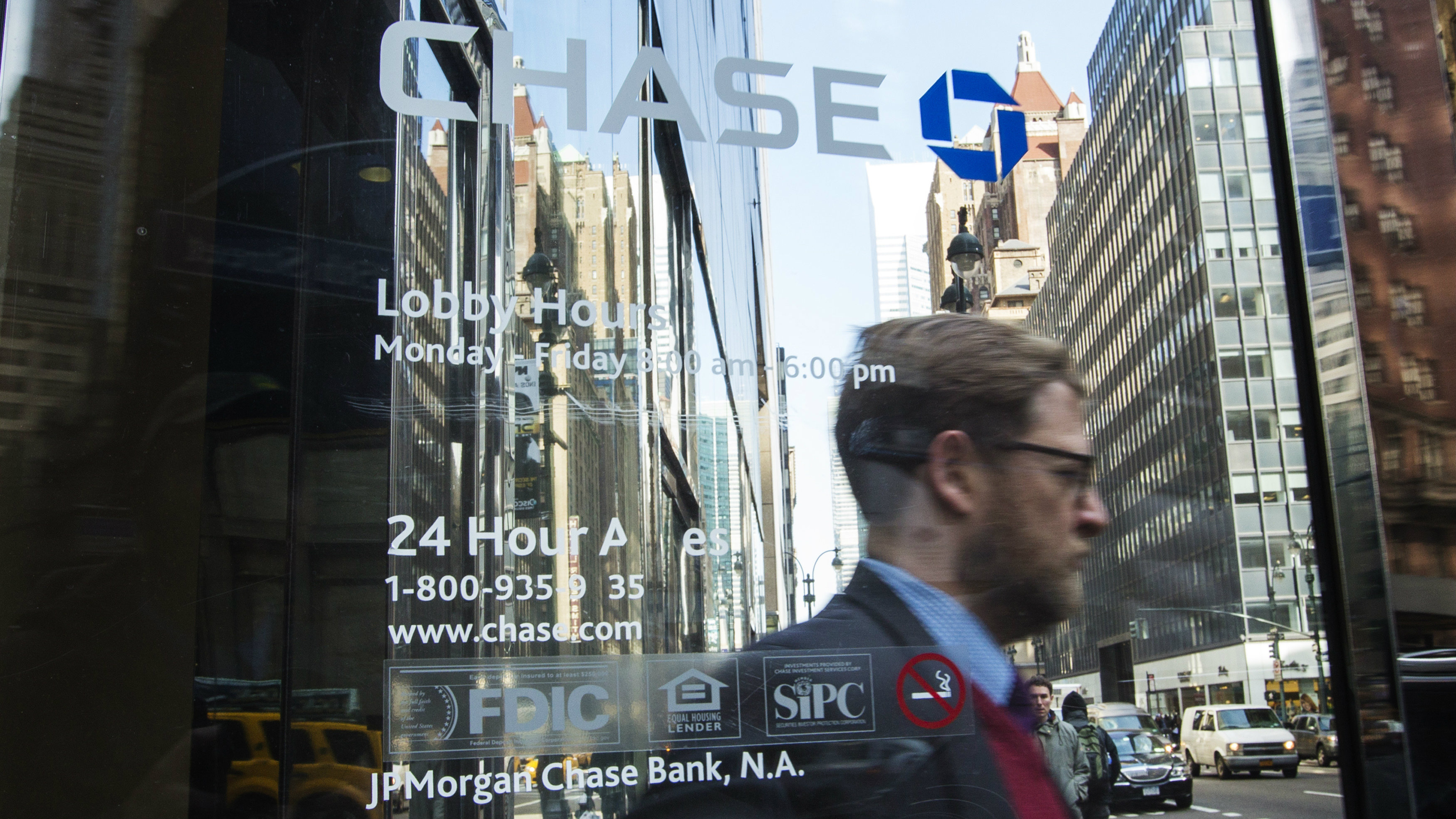 """A customer walks out of a branch of the JPMorgan Chase & Co bank in New York, March 15, 2013. A former JPMorgan Chase & Co executive in charge of the unit that made the disastrous """"London Whale"""" trades that became public last year, told lawmakers on Friday that she does not bear personal responsibility for the $6 billion in losses."""