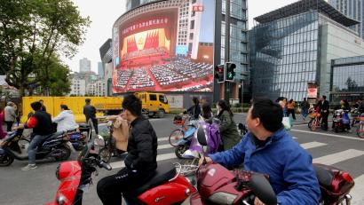 People watch a broadcast of Chinese President Xi Jinping delivering his speech during the opening of the 19th National Congress of the Communist Party of China, on a giant outdoor screen in Nanjing, Jiangsu province, China October 18, 2017. REUTERS/Stringer ATTENTION EDITORS - THIS IMAGE WAS PROVIDED BY A THIRD PARTY. CHINA OUT. - RC15E60F6D70