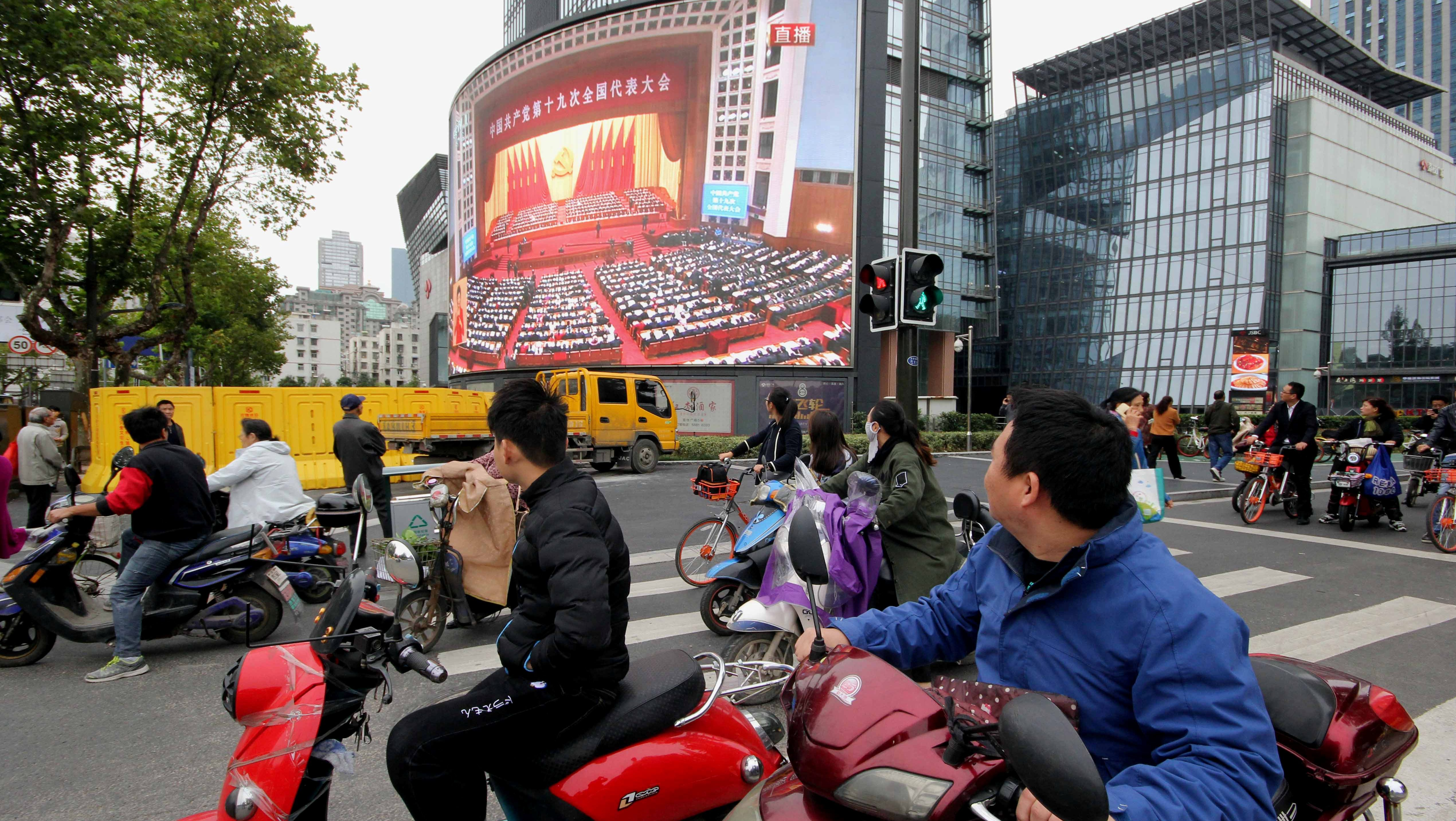 People watch a broadcast of Chinese President Xi Jinping delivering his speech during the opening of the 19th National Congress of the Communist Party of China, on a giant outdoor screen in Nanjing, Jiangsu province, China October 18, 2017. REUTERS/Stringer