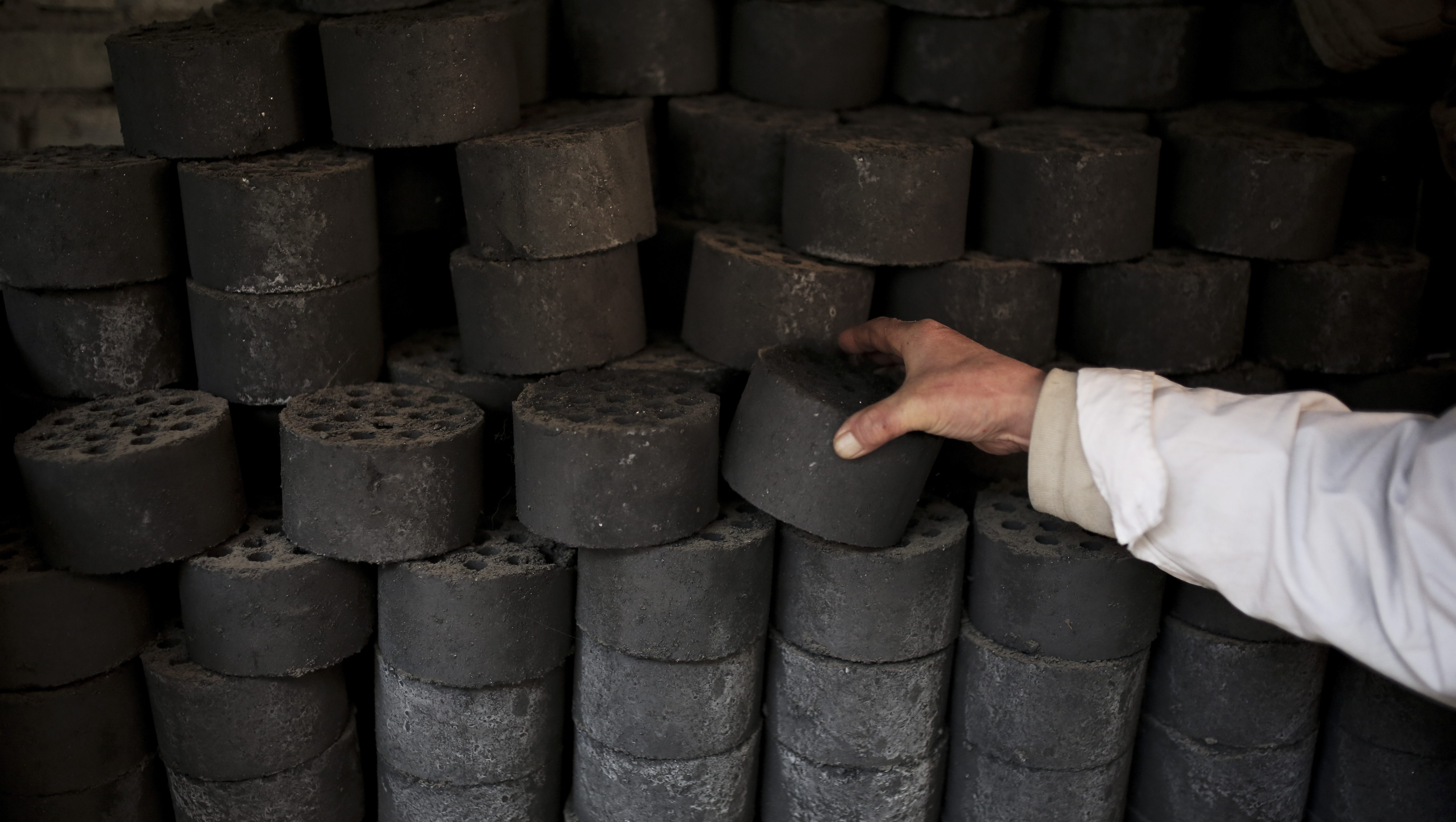 A man stocks up coal briquettes at his court yard, as many people living in old houses still rely on coal fire to heat up in the winter season, in Beijing, China Tuesday, Nov. 18, 2014. During APEC summit In China, U.S. President Barack Obama set an ambitious target for cutting U.S. emissions in a landmark deal in which China will also rein in its emissions. In Australia G20 summit, he pledged $3 billion to help poorer nations address changing temperatures. (AP Photo/Andy Wong)