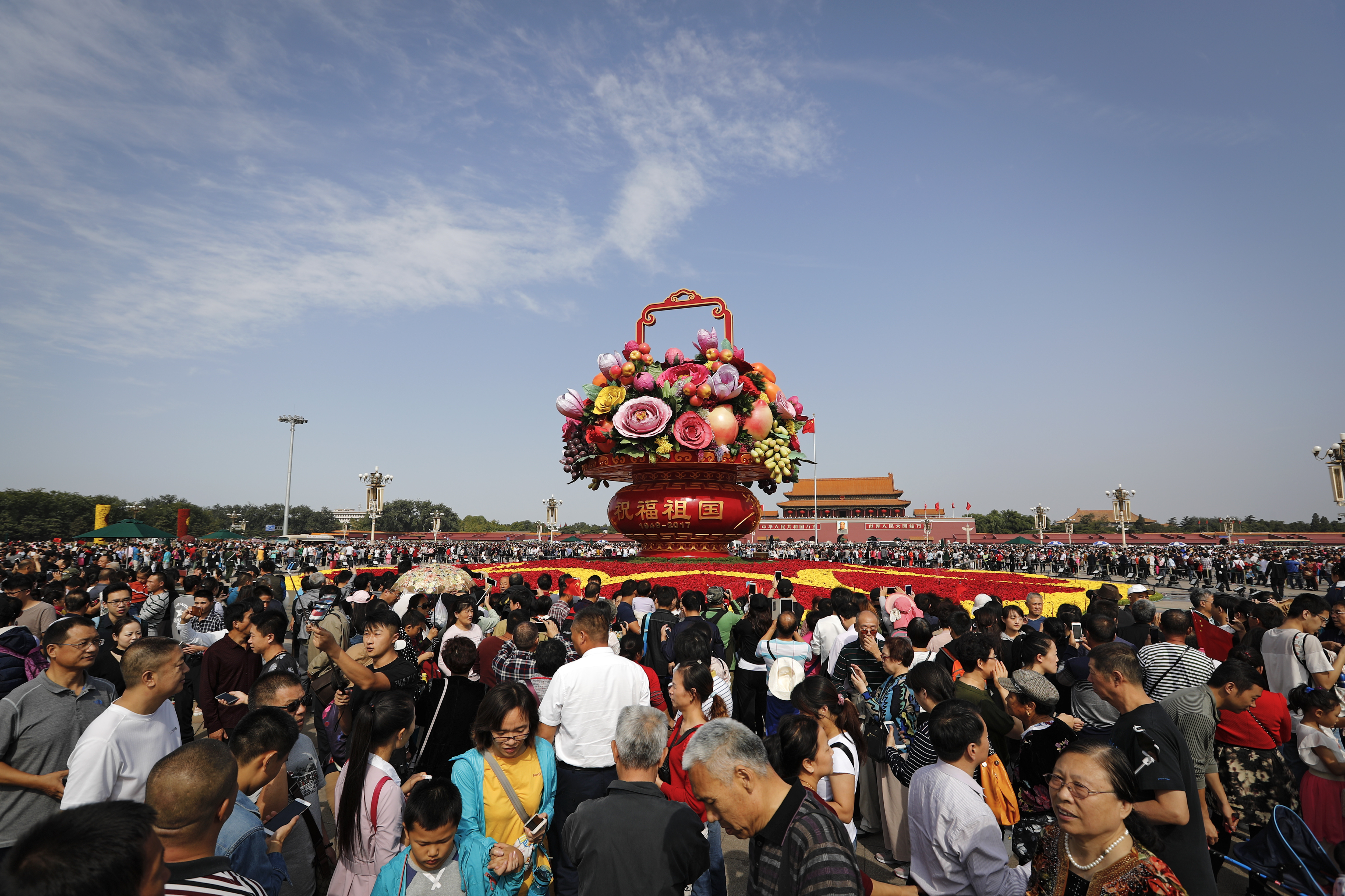 Visitors gather near a giant basket decorated with replicas of flowers and fruits on display at Tiananmen Square on China's National Day in Beijing, Sunday, Oct. 1, 2017. Hundreds of thousands foreign and domestic tourists flock to the square to celebrate the 68th National Day and the Mid-Autumn Festival over the week-long holidays.