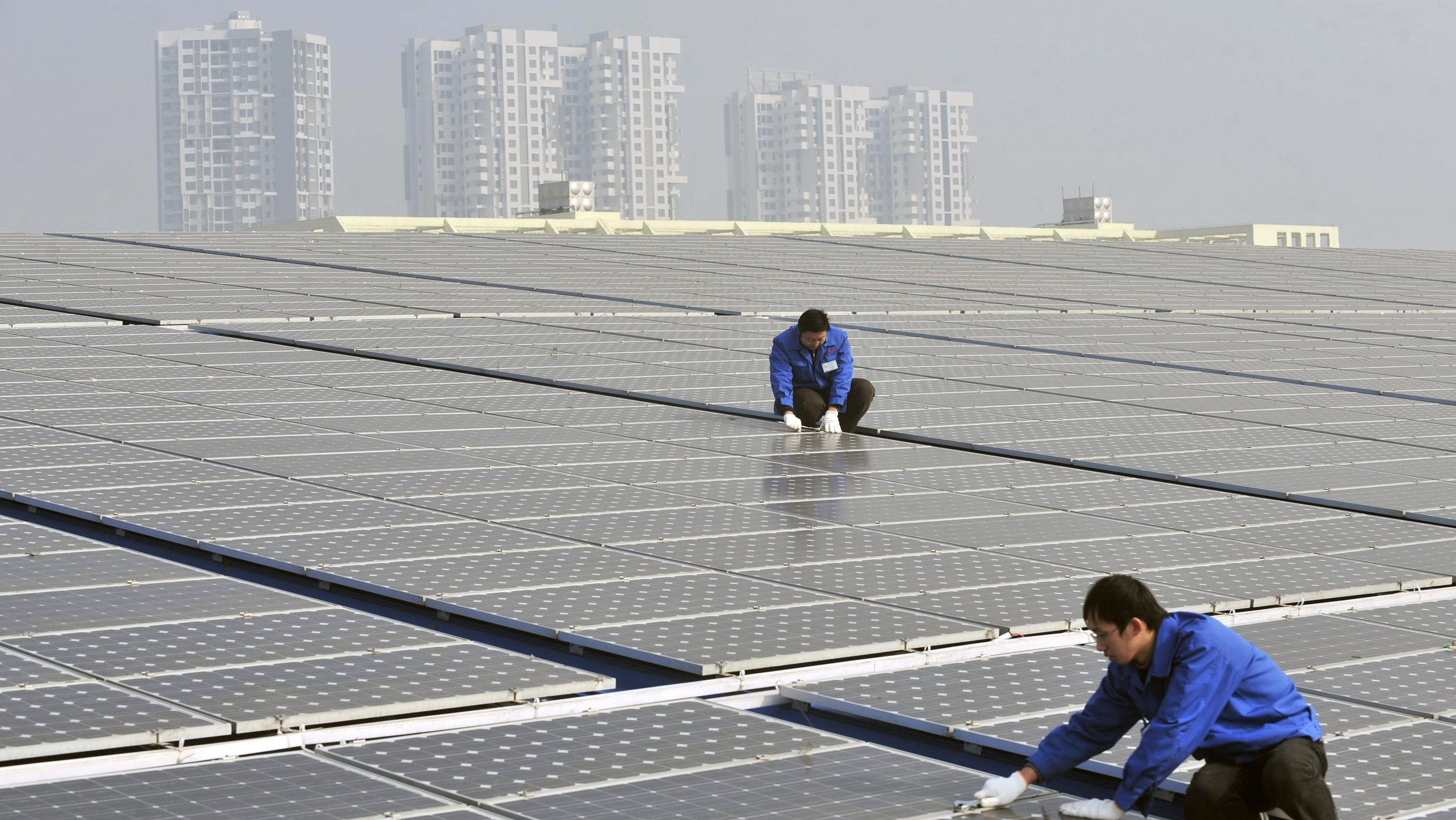 Technicians maintain solar panels on a roof at a solar power plant in Wuhan, Hubei province, January 12, 2010. The Chinese government aims to boost renewable energy generating capacity in the country, with plans to produce at least 10,000 MW of solar energy and 20,000 MW of wind power by 2020. Picture taken January 12, 2010. REUTERS/China Daily