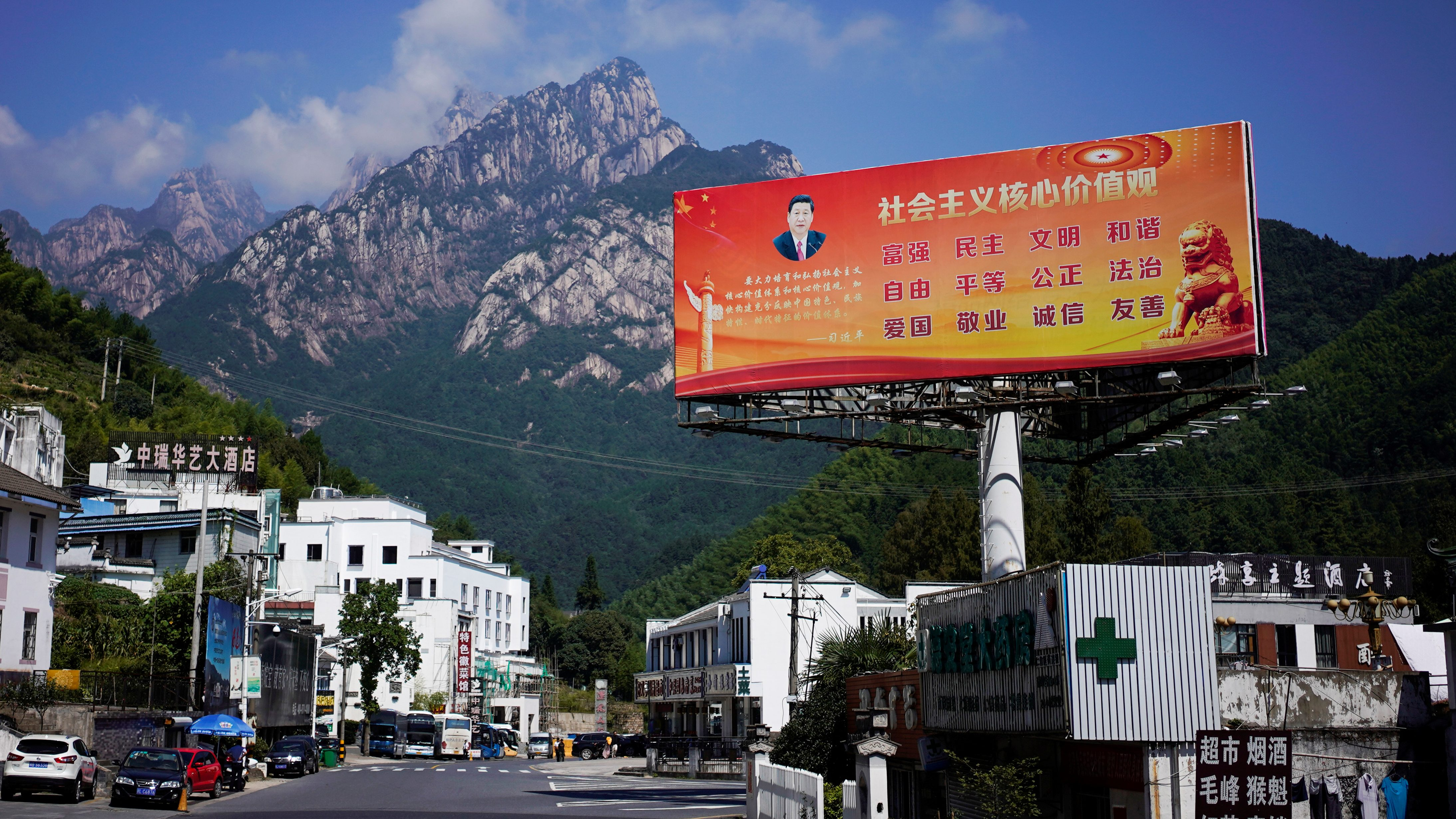 """A poster with a portrait of Chinese President Xi Jinping overlooks a street in Huangshan, Anhui province, China, September 16, 2017. The slogan reads: """"Core Socialist Values: prosperity, democracy, civility, and harmony; freedom, equality, justice, rule of law; patriotism, dedication, integrity and friendship.""""  Picture taken September 16, 2017.  REUTERS/Aly Song - RC1A87FE6EA0"""