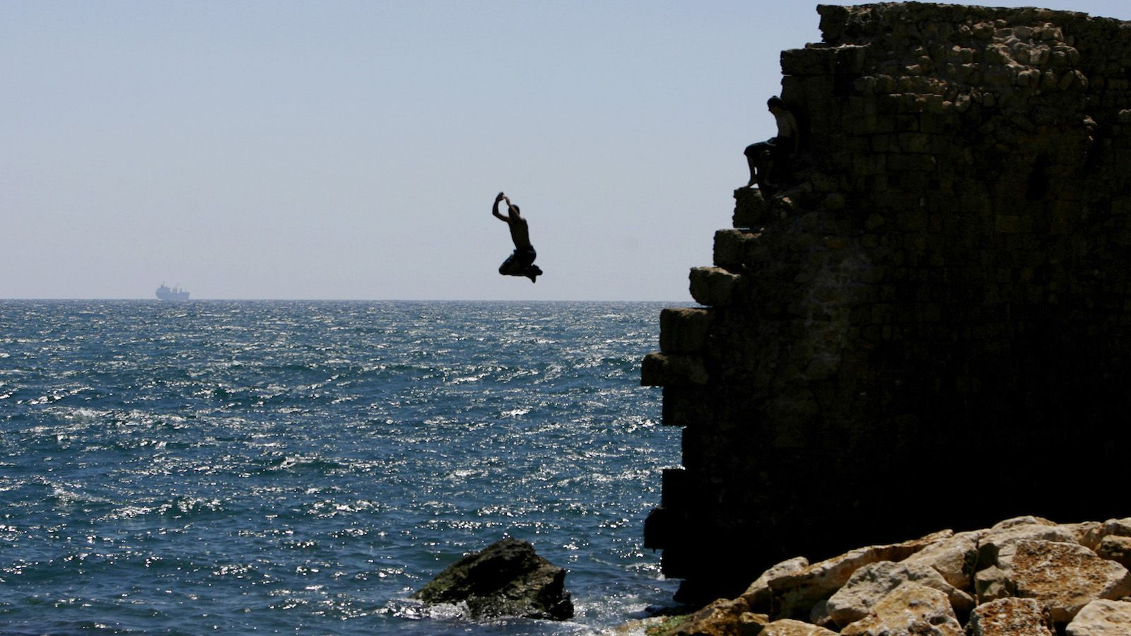 person diving off cliff