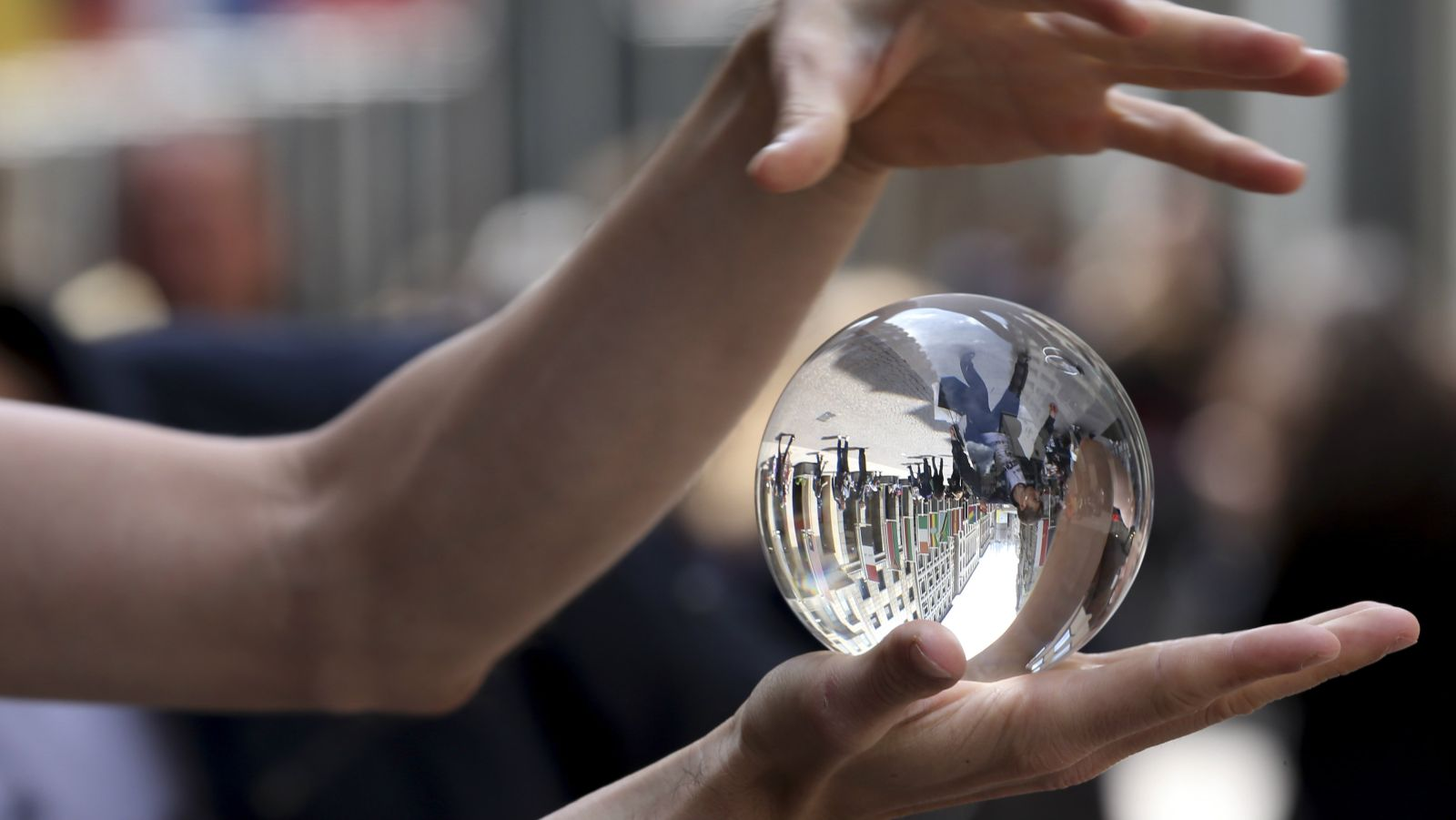 Tom Atto, a street artist from Slovakia, performs with a crystal ball in Milan, Italy, Wednesday, May 29, 2013. (AP Photo/Luca Bruno)