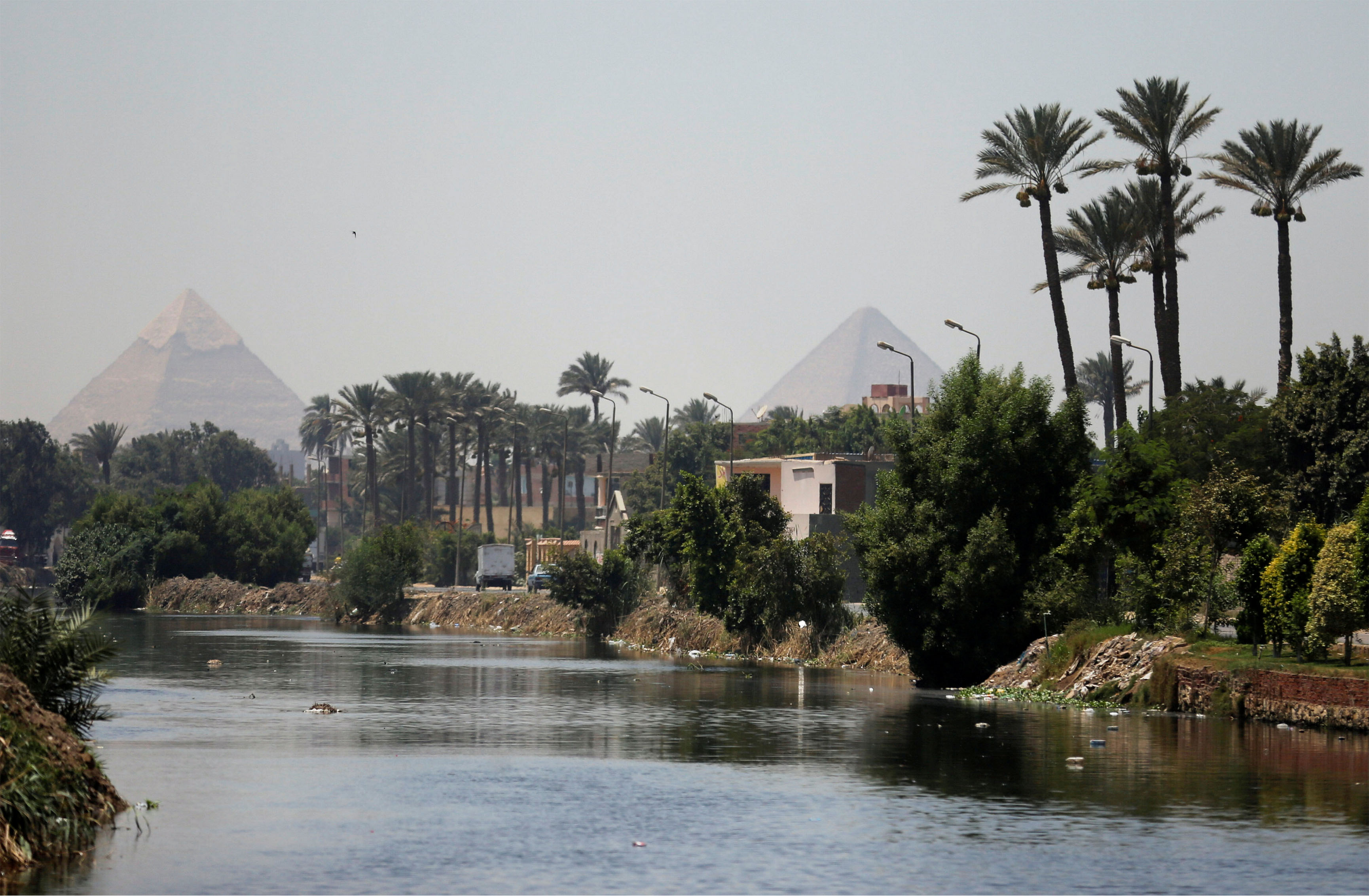 The Great Giza pyramids are seen behind a canal which flows into the River Nile on the outskirts of Cairo, Egypt August 1, 2017.