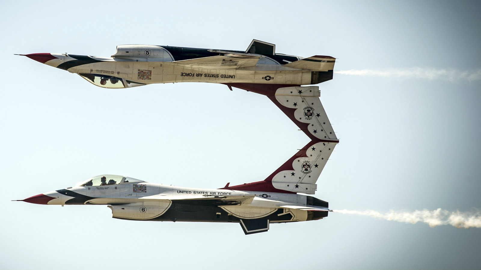 US Air Force pilots with the Thunderbirds perform the calypso pass maneuver in F-16 Fighting Falcon aircraft over the Mountain Home Air Force Base, Idaho in September 2014.