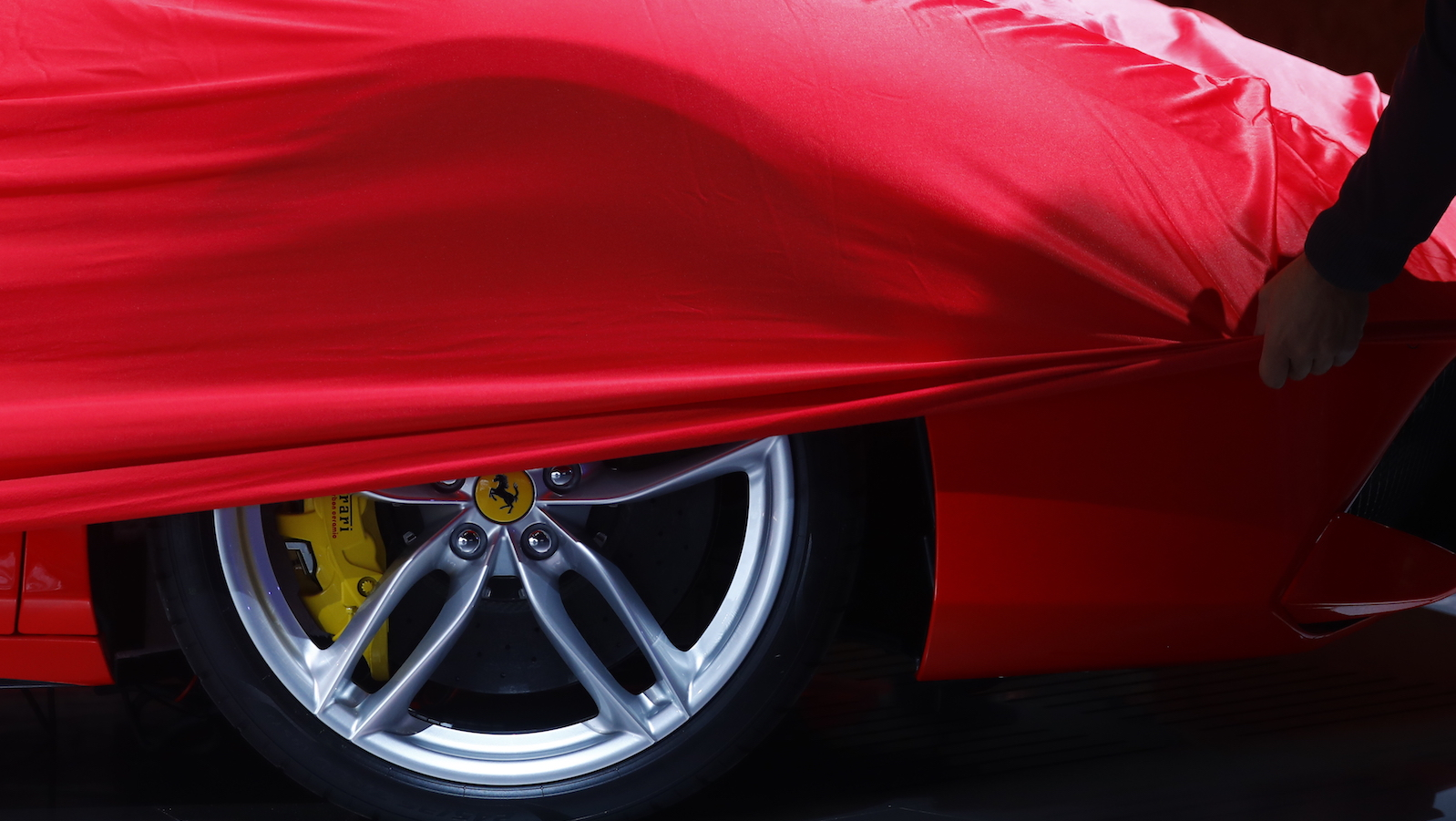 A partially covered Ferrari car is pictured before the opening of the Frankfurt Motor Show