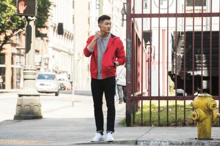 Asian man in street clothing wearing a red sweater in a city setting on the street. He's wearing flyer in nightfall blue and ionic in blue gray and silver gray.