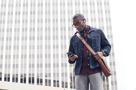 Young black man in street clothes wearing flyer in lunar gray and ionic with the congnac leather band checking his cell phone.