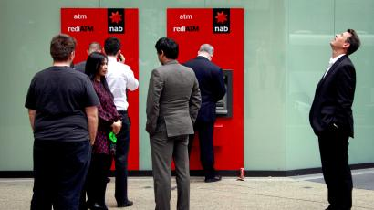 A man looks up as he stands next to a line for two National Australia Bank Ltd (NAB) automatic teller machines (ATMs) in central Sydney in this picture taken August 23, 2013.