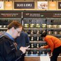 Shoppers roam through an Amazon Go store, currently open only to Amazon employees, in Seattle. Amazon Go shops are convenience stores that don't use cashiers or checkout lines, but use a tracking system that of sensors, algorithms, and cameras to determine what a customer has bought. Amazon's nearly $14 billion deal for Whole Foods isn't just about getting more than 460 grocery stores. Ultimately, Amazon wants to sell Amazon and Whole Foods shoppers alike even more goods and services, including stuff they might not even realize they need. (AP Photo/Elaine Thompson, File)