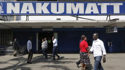 Pedestrians walk in front of closed shutters of a Nakumatt supermarket branch in downtown Nairobi, Kenya, 19 September 2017. Kenya's struggling supermarket chain Nakumatt said on 18 September that it has signed a merger deal with the country's biggest retailer Tuskys to turn around its operations. Nakumatt has closed some of the branches in recent months due to its financial problems.