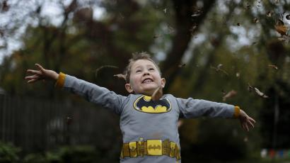 Benjamin Rocamp, who dressed as Batman, celebrates Halloween at the Flint family's annual Halloween block party in Silver Spring, Maryland October 31, 2014. The Flint family have decorated their house and thrown a theme block party for the last 17 years for neighborhood children and adults before the annual trick or treating.