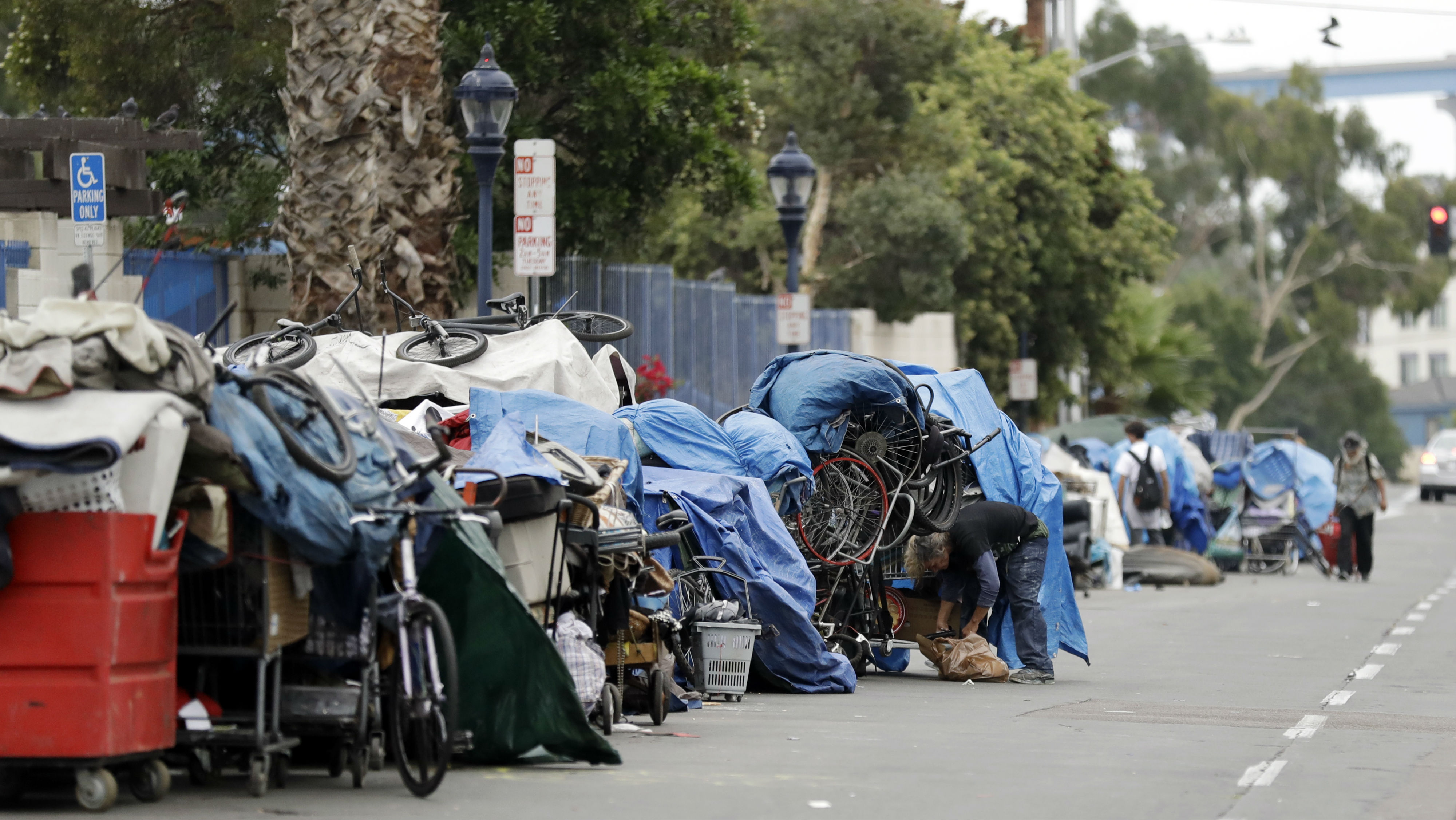 In this Sept. 19, 2017 photo, homeless people stand among their items along 17th Street in San Diego. The city has cleared a downtown street where hundreds of homeless people regularly camp during ongoing efforts to sanitize neighborhoods to control the spread of hepatitis A.