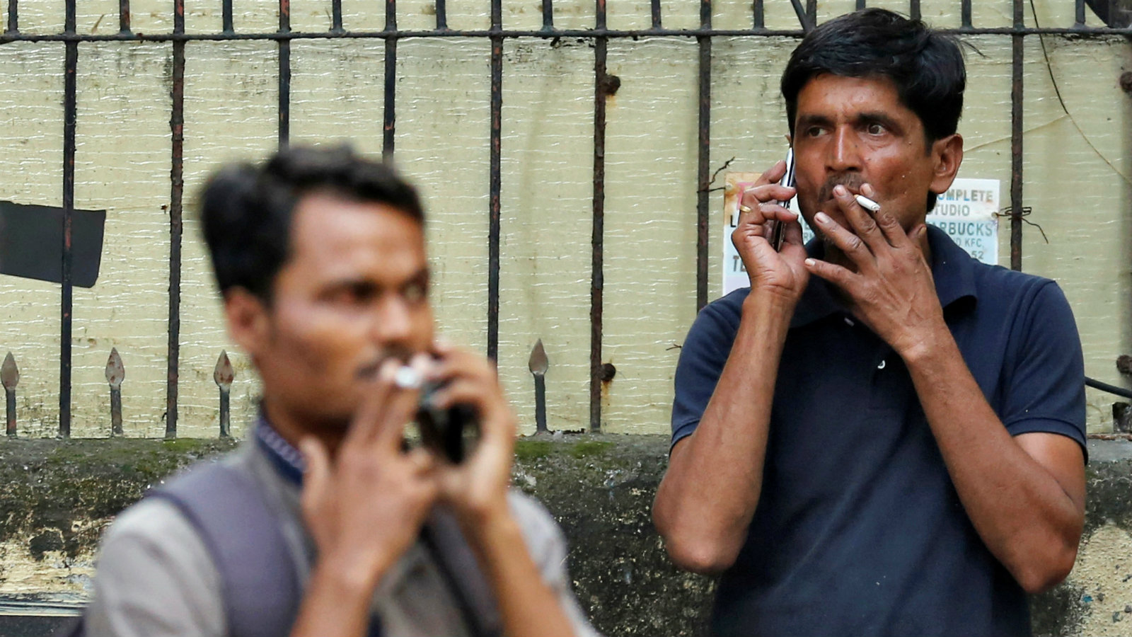 People smoke cigarettes along a road in Mumbai, India, October 26, 2016. Picture taken October 26, 2016.