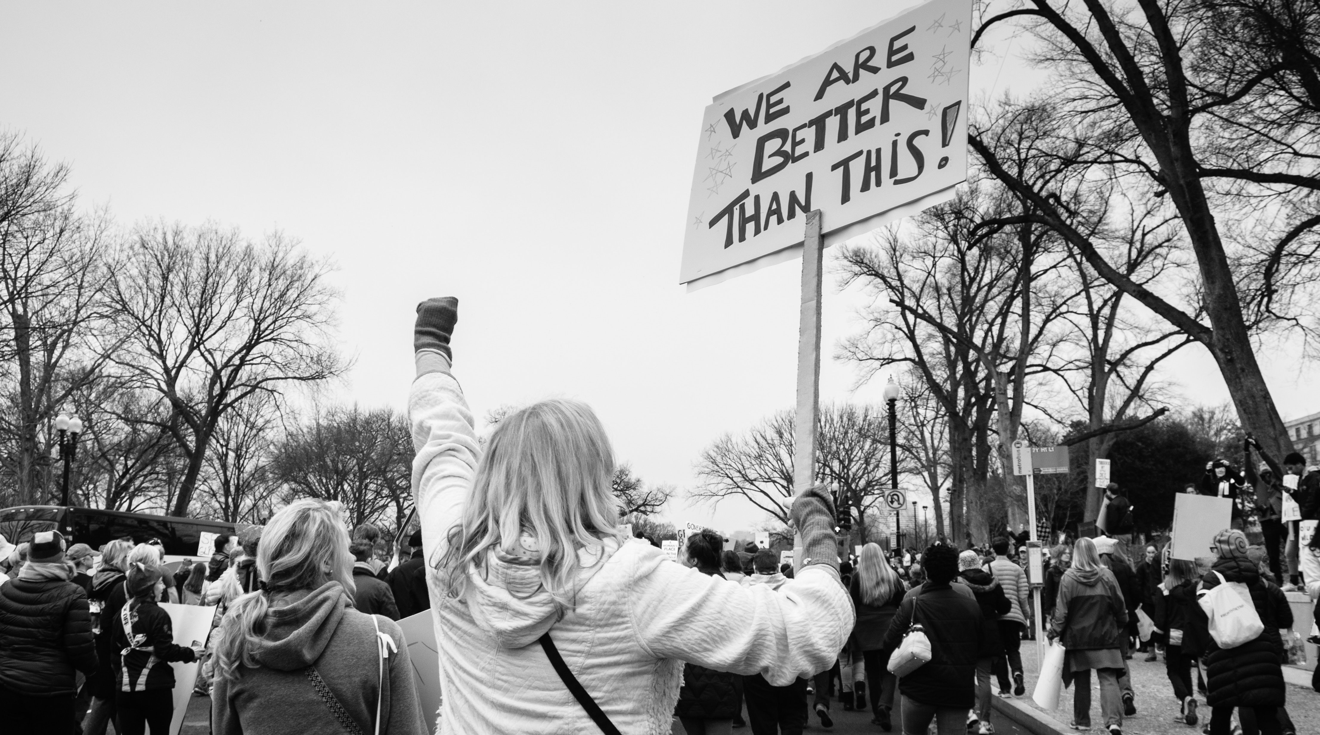 """A woman marches in the women's march holding a sign that says """"We are better than this."""""""