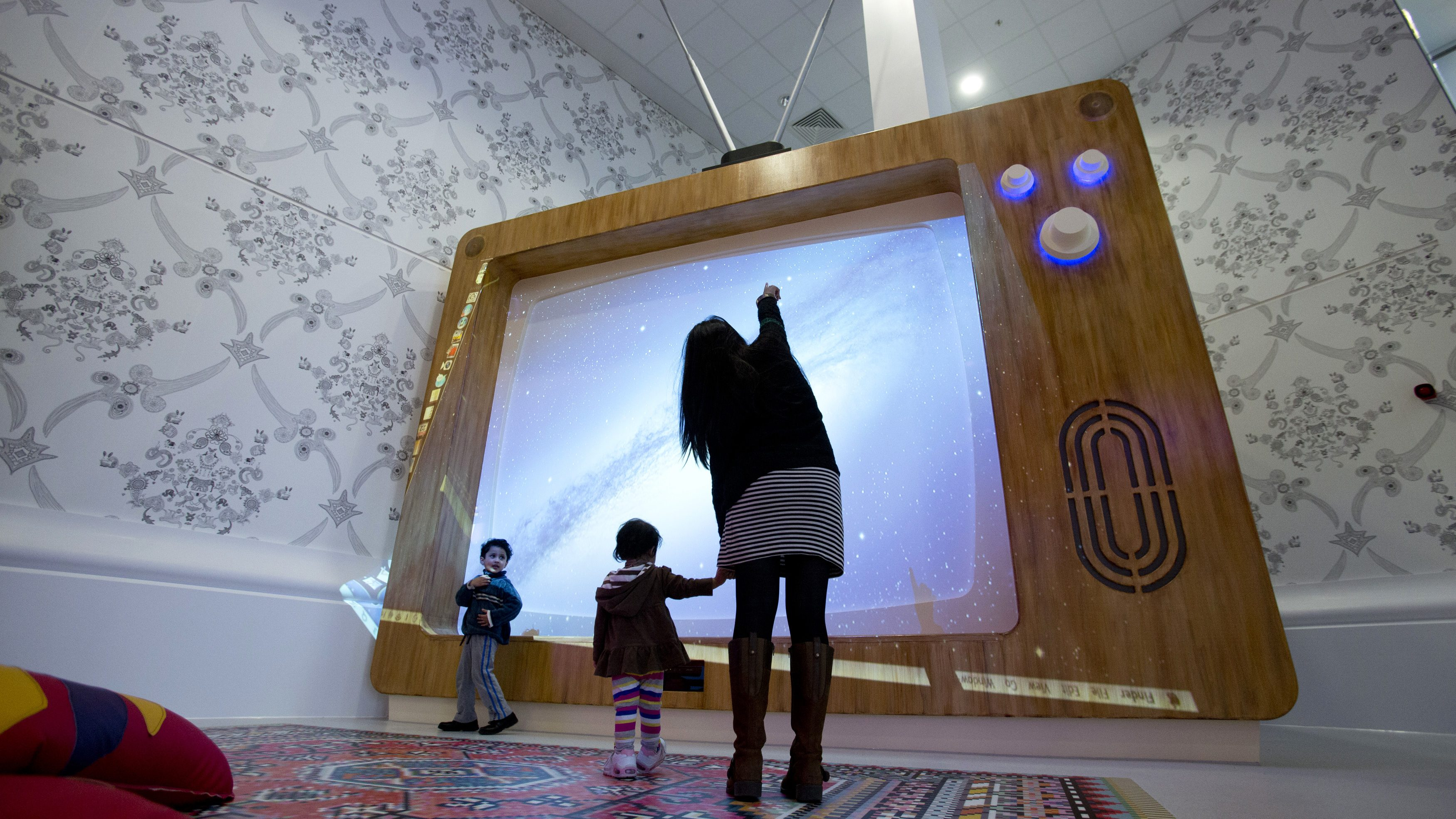 A woman and young children interact with a giant television set