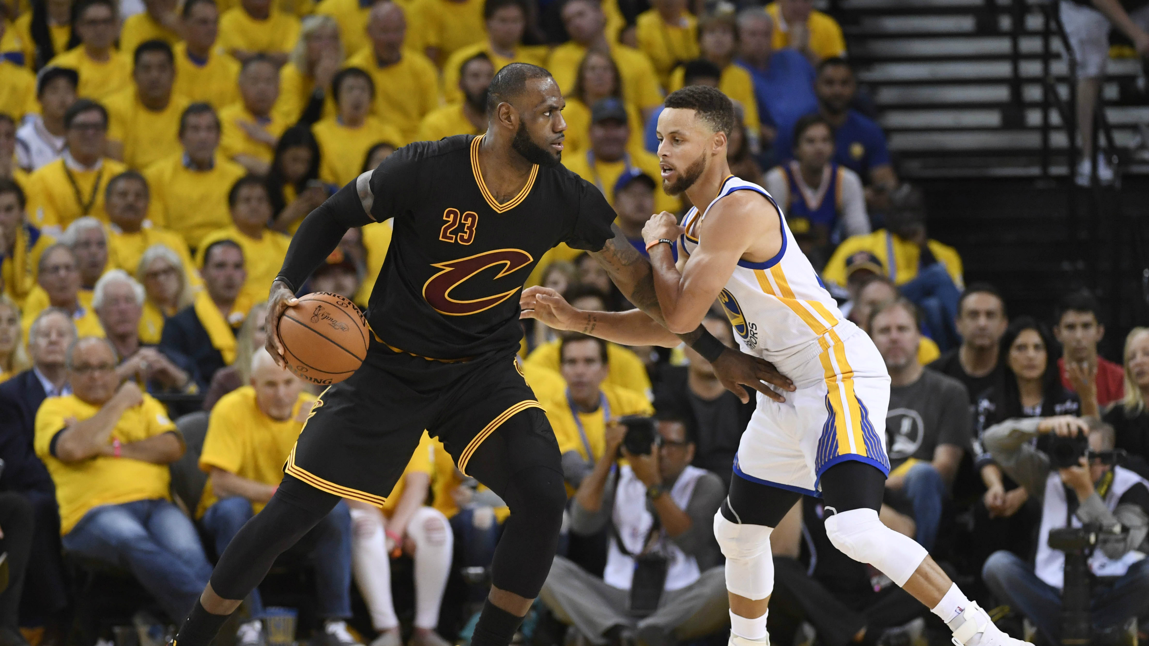 Lebron James and Stephen Curry on a basketball court.